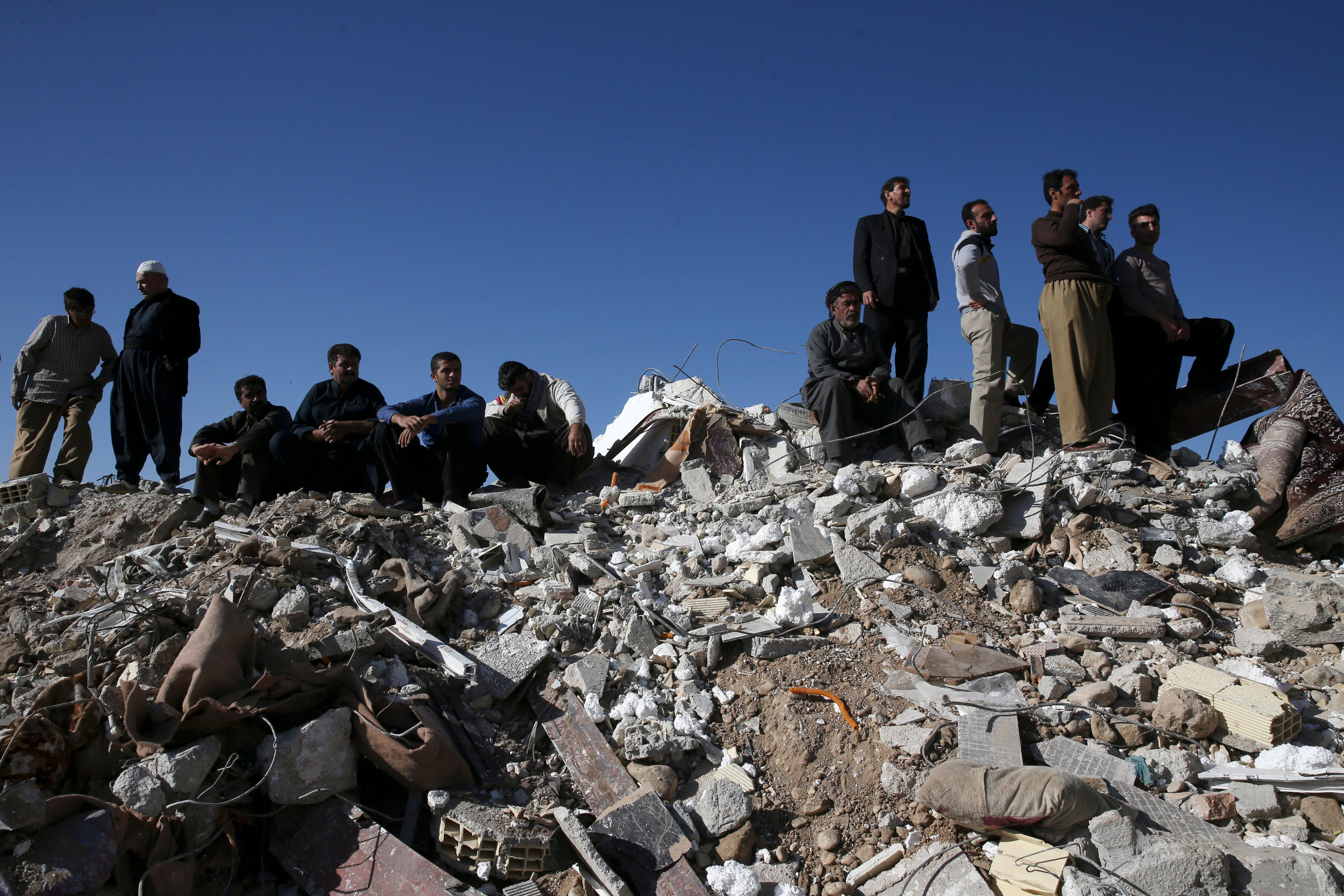 Survivors sit on the debris while rescuers search on the earthquake site in Sarpol-e-Zahab in western Iran, Tuesday, Nov. 14, 2017. Rescuers on Tuesday used backhoes and heavy equipment to dig through the debris of buildings toppled by a powerful earthquake on the border between Iran and Iraq. (AP Photo/Vahid Salemi)