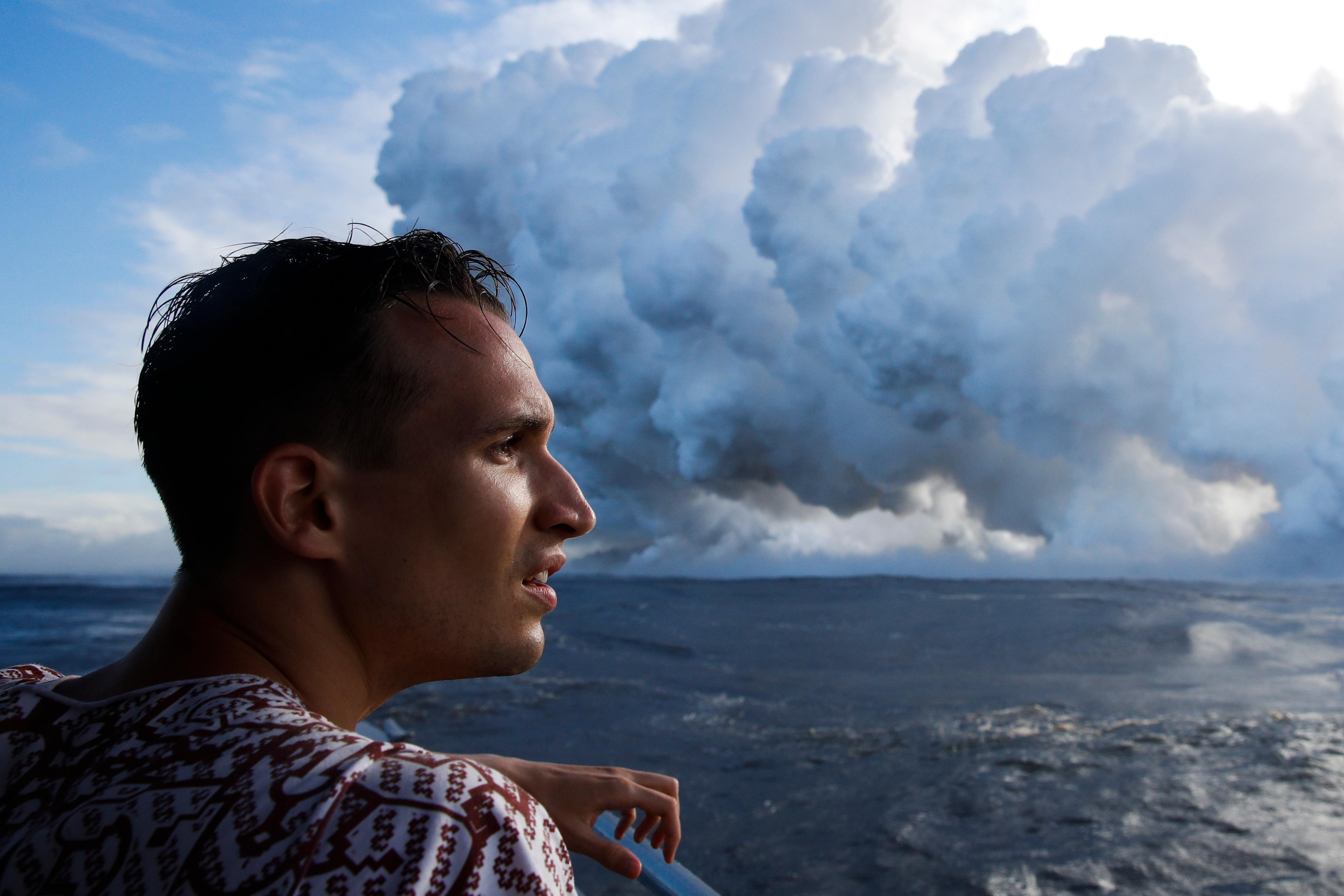 Gabor Kovacs, visiting from Hungary, watches as lava flows into the ocean, generating plumes of steam, near Pahoa, Hawaii Sunday, May 20, 2018. Kilauea volcano that is oozing, spewing and exploding on Hawaii's Big Island has gotten more hazardous in recent days, with rivers of molten rock pouring into the ocean Sunday and flying lava causing the first major injury. (AP Photo/Jae C. Hong)