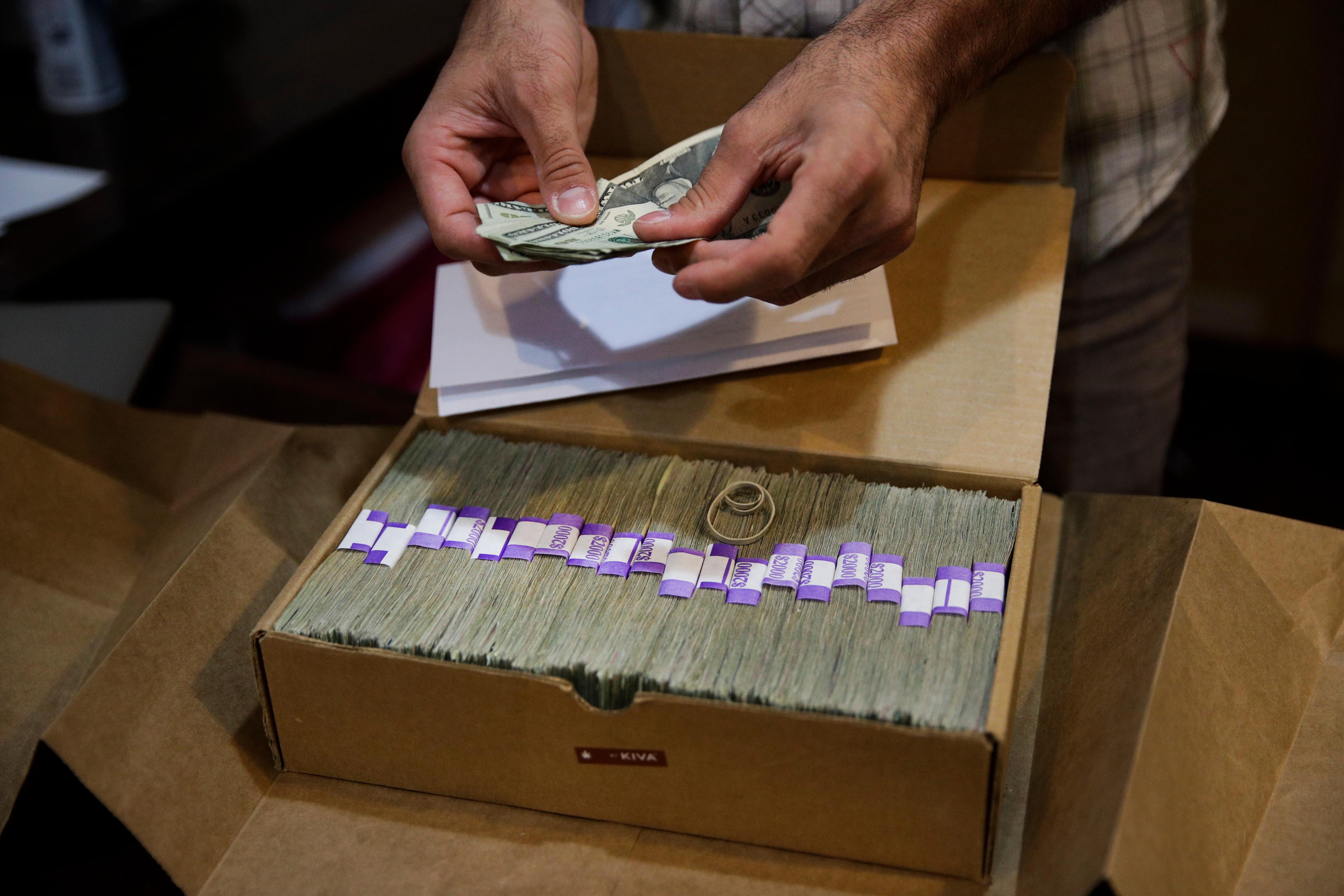 FILE - In this June 27, 2017, file photo, an owner of a medical marijuana dispensary in Los Angeles prepares his monthly tax payment. (AP Photo/Jae C. Hong,File)