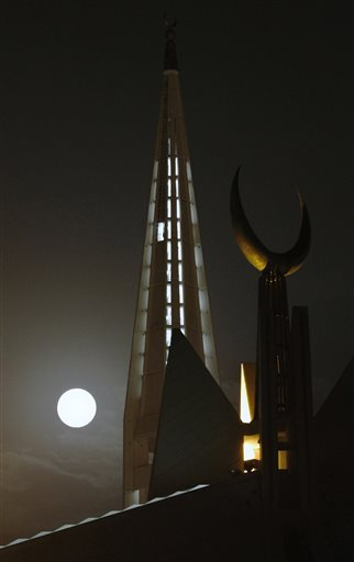 A perigee moon, also known as a supermoon, looks over the grand Faisal mosque in Islamabad, Pakistan,Saturday, July 12, 2014.