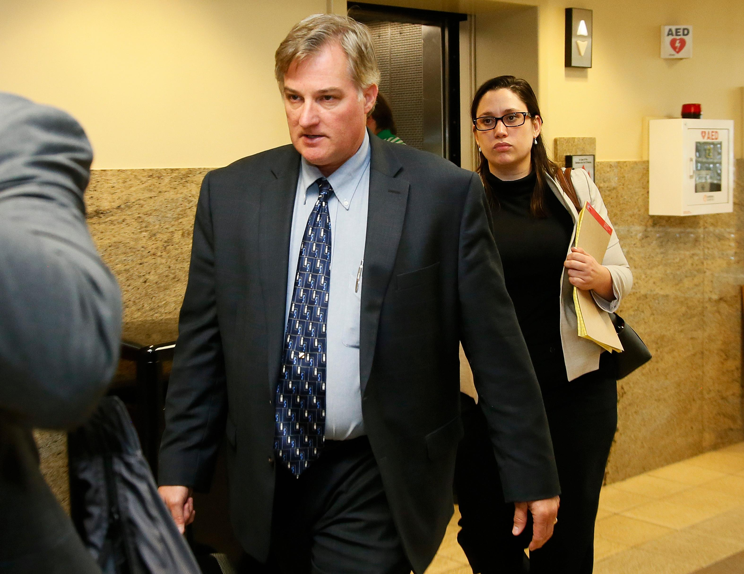 In this Friday, June 30, 2017 photo, Shannon Kepler, left, arrives with his legal team for afternoon testimony in his trial in Tulsa, Okla. Kepler, a former Oklahoma police officer who fatally shot his daughter's black boyfriend in 2014 is on trial for the third time after jurors in previous trials couldn't decide whether or not to convict him of first-degree murder. (AP Photo/Sue Ogrocki)