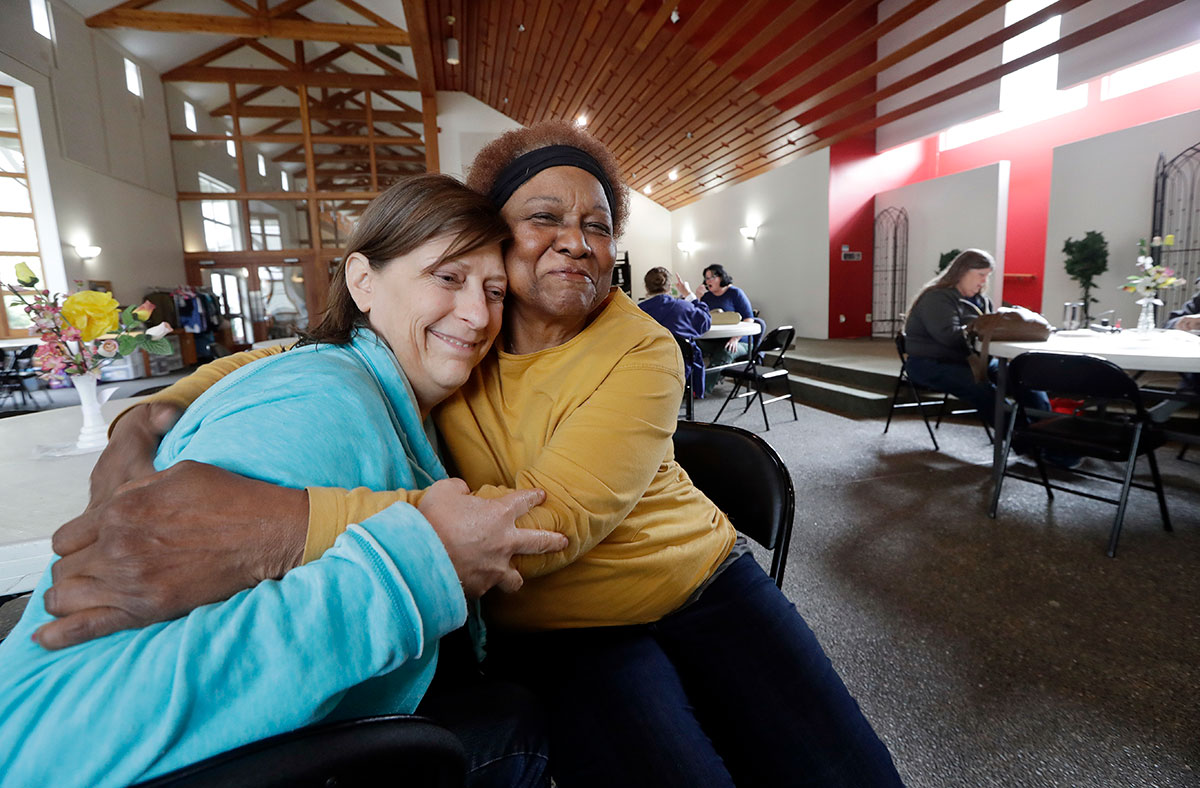 In this Monday, March 5, 2018, photo, Patrice E., right, who declined to provide her last name, embraces her friend Ronda Rohde inside a church building where they are among the two-dozen women living in their vehicles in the adjacent parking lot in Kirkland, Wash. Some of the obstacles faced by the women in finding permanent housing may soon become illegal in Washington state, where legislators are advancing a bill that would prohibit landlords from turning away tenants who rely on Section 8 vouchers, Social Security or veterans benefits. (AP Photo/Elaine Thompson)