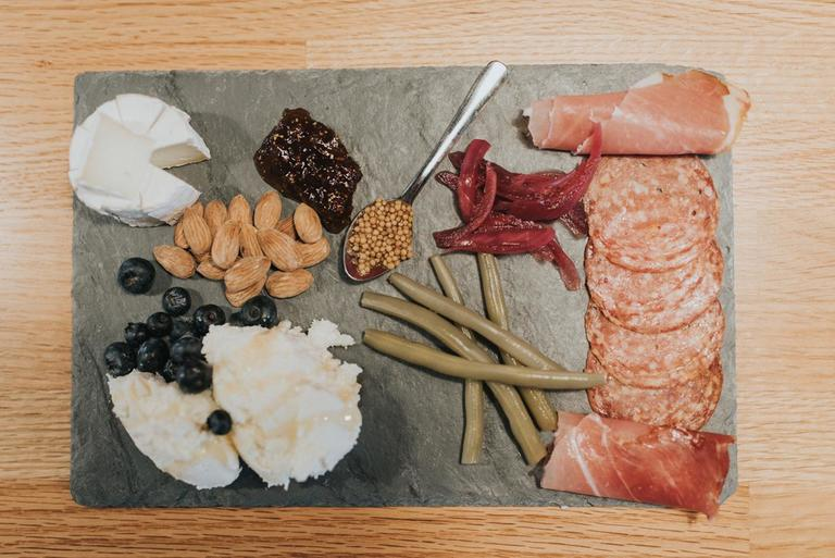 Cheese board featuring: Misty River Camembert-style cheese, fig jam, bread, house pickled red onions, prosciutto, almonds, house pickled green beans, salami, Urban Stead Quark with local honey and blueberries, and house pickled mustard seeds / Image: Brianna Long // Published: 4.11.18<p></p>