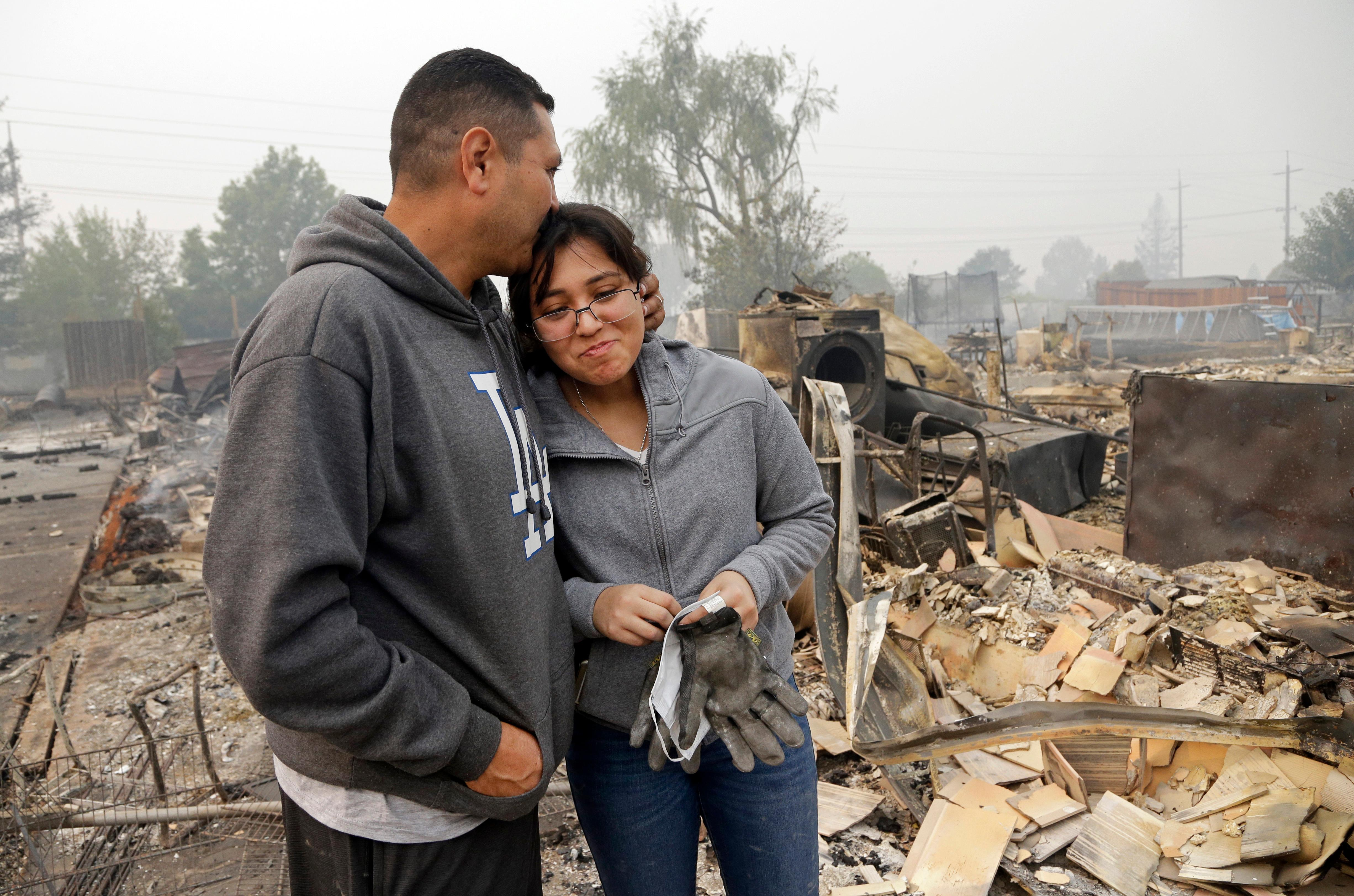Jose Garnica, left, kisses his daughter Leslie Garnica in front of their home that was destroyed in the Coffey Park area of Santa Rosa, Calif., on Tuesday, Oct. 10, 2017. An onslaught of wildfires across a wide swath of Northern California broke out almost simultaneously then grew exponentially, swallowing up properties from wineries to trailer parks and tearing through both tiny rural towns and urban subdivisions. (AP Photo/Ben Margot)