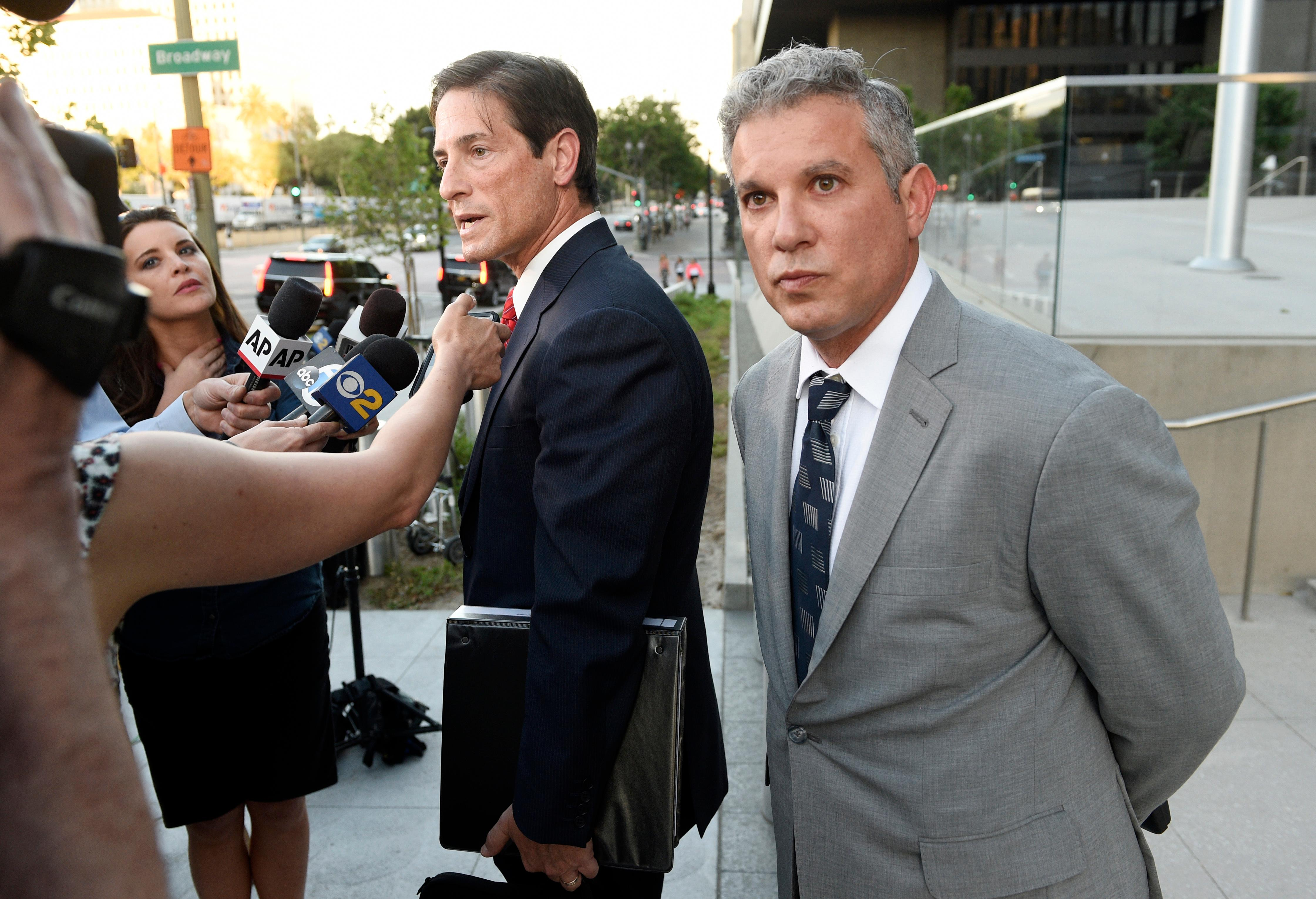 Jonathan Todd Schwartz, right, former business manager for singer Alanis Morissette, looks on as his attorney Nathan Hoffman addresses reporters outside U.S. federal court following sentencing in his embezzlement case, Wednesday, May 3, 2017, in Los Angeles. Schwartz was sentenced to six years in federal prison for stealing more than $7 million from the singer and other clients, and was ordered to pay $8.6 million in restitution. (AP Photo/Chris Pizzello)