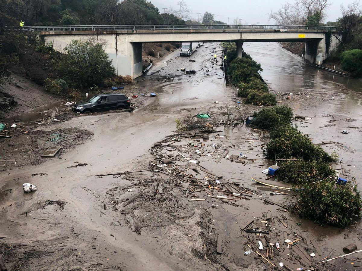 In this photo provided by Santa Barbara County Fire Department, U.S. Highway 101 at the Olive Mill Road overpass is flooded with runoff water from Montecito Creek in Montecito, Calif. on Tuesday, Jan. 9, 2018. Dozens of homes were swept away or heavily damaged Tuesday as downpours sent mud and boulders roaring down hills stripped of vegetation by a gigantic wildfire that raged in Southern California last month. (Mike Eliason/Santa Barbara County Fire Department via AP)