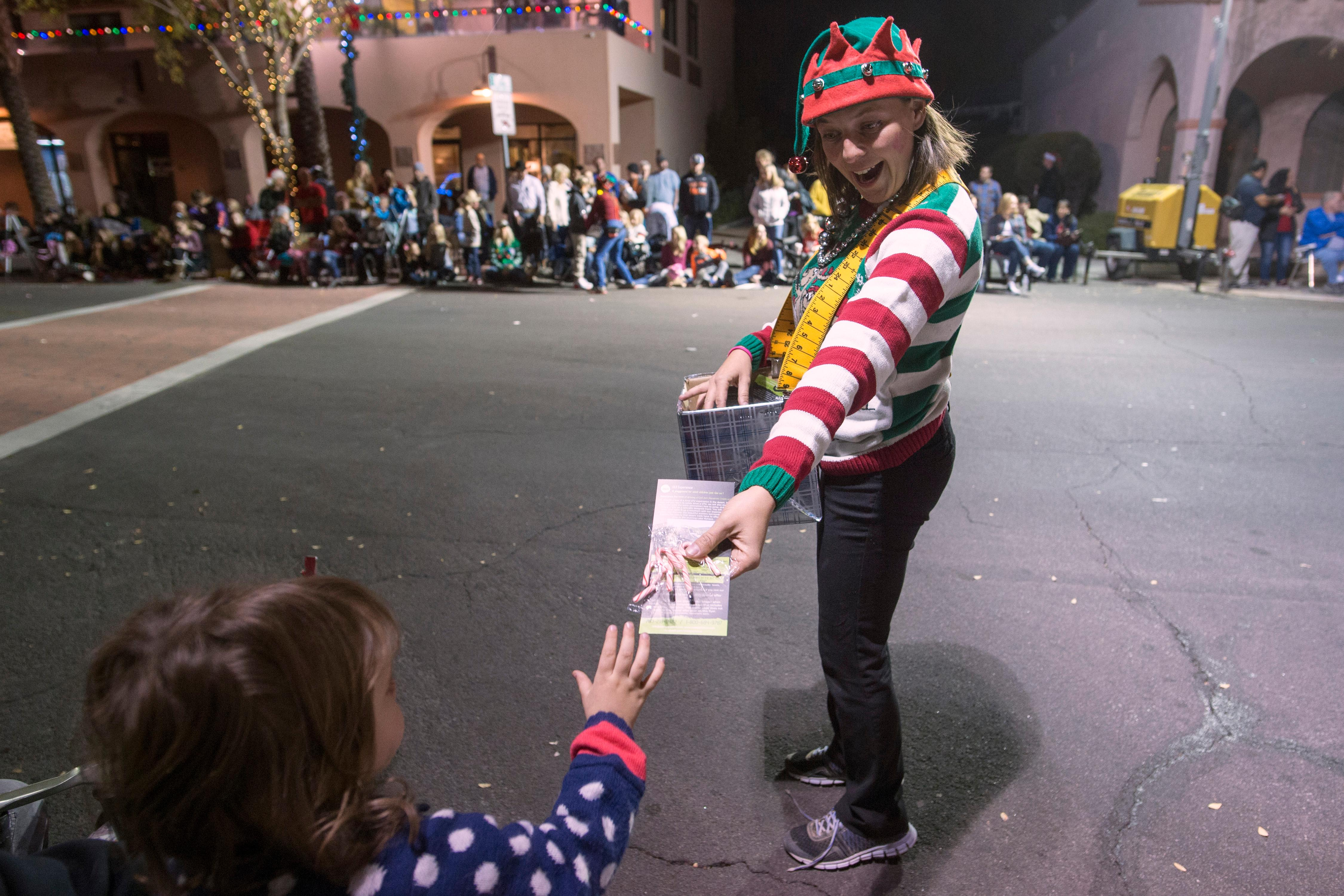 A woman dressed as an elf hands out candy during the Santa's Electric Parade Saturday, December 2, 2017, in Boulder City. [Sam Morris/Las Vegas News Bureau]