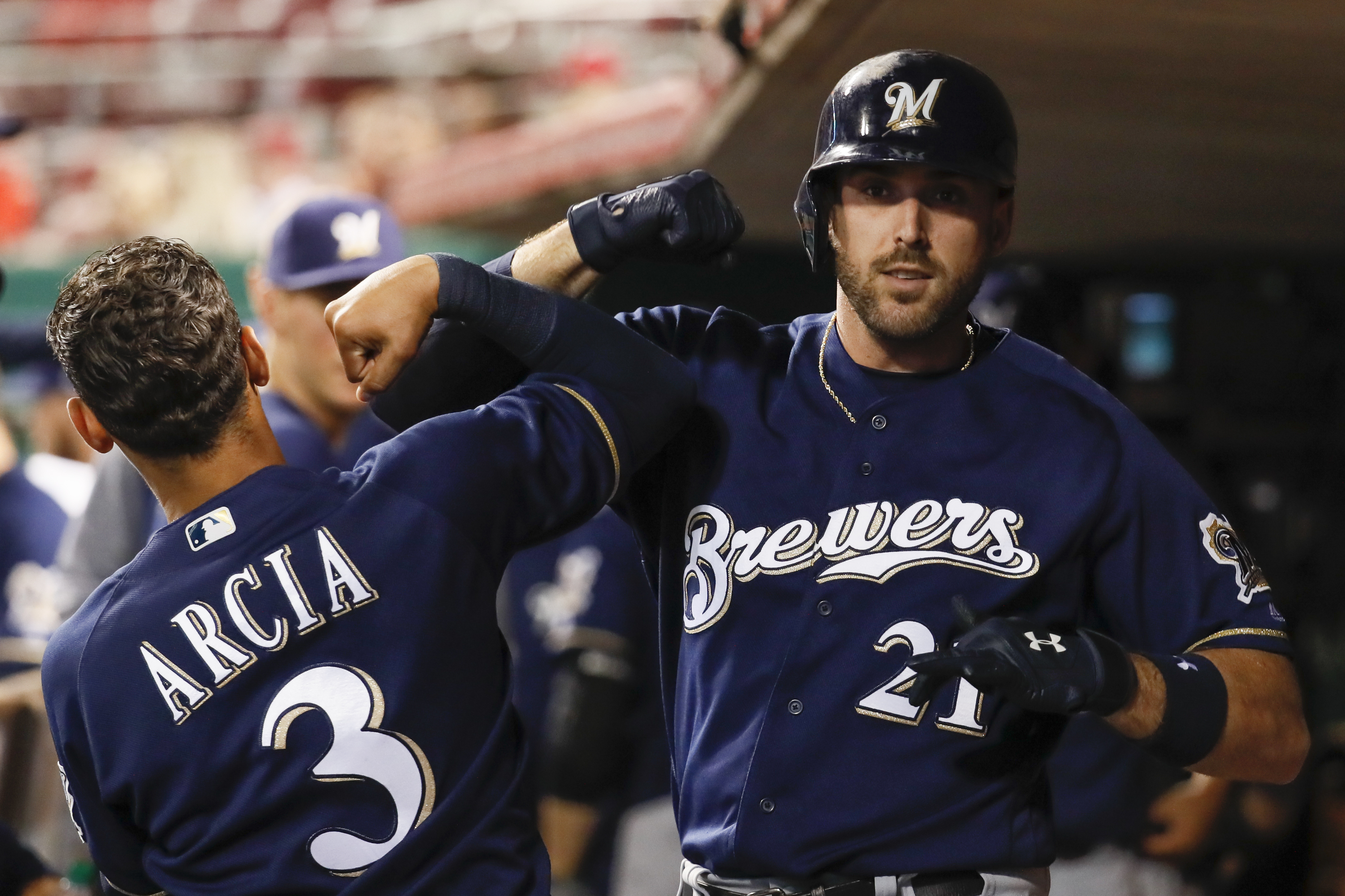 Milwaukee Brewers' Travis Shaw (21) celebrates in the dugout with Orlando Arcia (3) after hitting a two-run home run off Cincinnati Reds relief pitcher Ariel Hernandez during the eighth inning Tuesday, Sept. 5, 2017, in Cincinnati. (AP Photo/John Minchillo)
