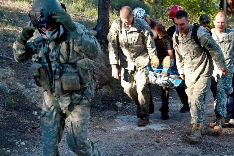 Soldiers and civilian rescue personnel use a rescue basket to carry an elderly man on oxygen to a UH-60 Black Hawk helicopter in Glen Haven, Colo., Sept. 16, 2013, in support of flood relief operations in Larimer County.