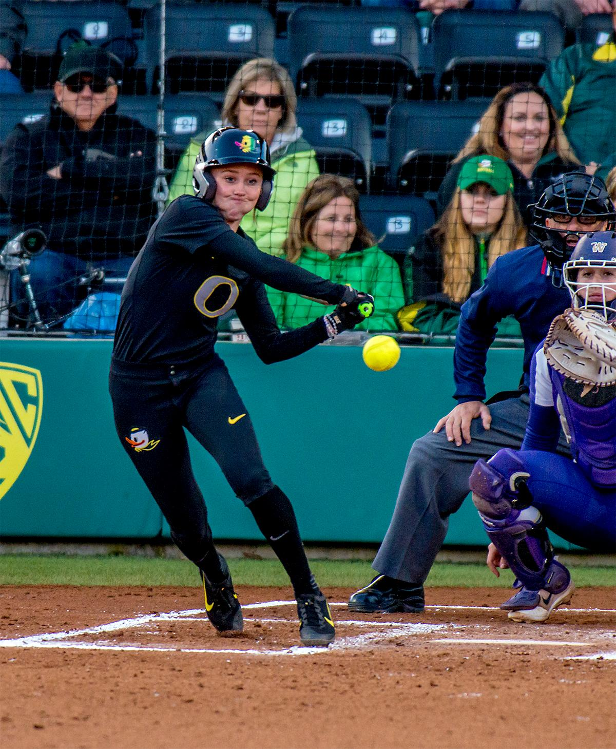 The Duck's Alexis Mack (#10) keeps her eyes on the ball as she goes for the swing. In Game Two of a three-game series, the University of Oregon Ducks softball team defeated the University of Washington Huskies 4-1 Friday night in Jane Sanders Stadium. Danica Mercado (#2), Alexis Mack (#10) and Mia Camuso (#7) all scored in the win, Mack twice. The Ducks play the Huskies for the tie breaker on Saturday with the first pitch at noon. Photo by August Frank, Oregon News Lab
