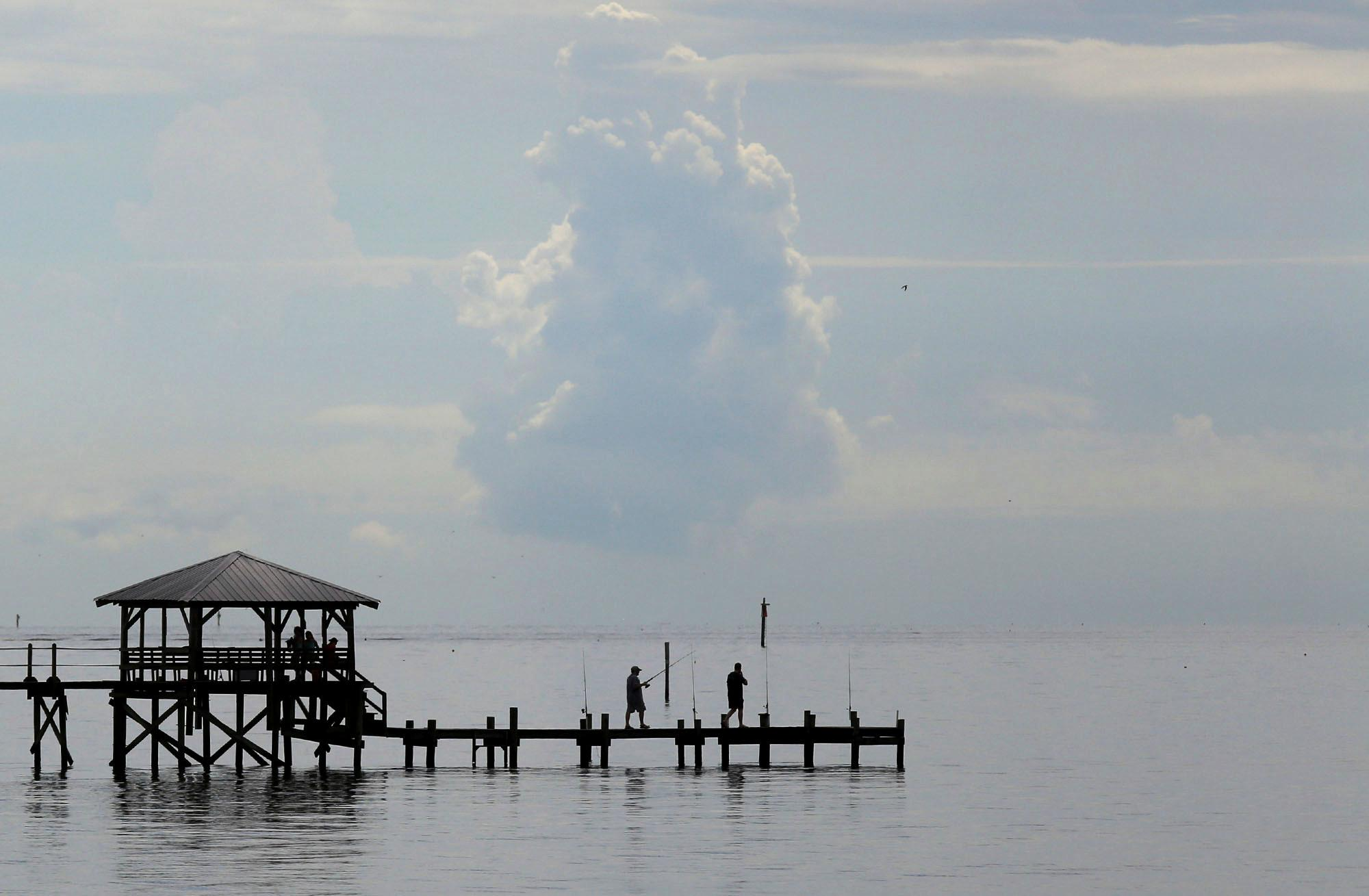 A pair of fishermen walk out on a pier in Pass Christian, Miss., on Friday May 24, 2018. Heavy rains are expected over the Memorial Day weekend in south Mississippi. (John Fitzhugh/The Sun Herald via AP)