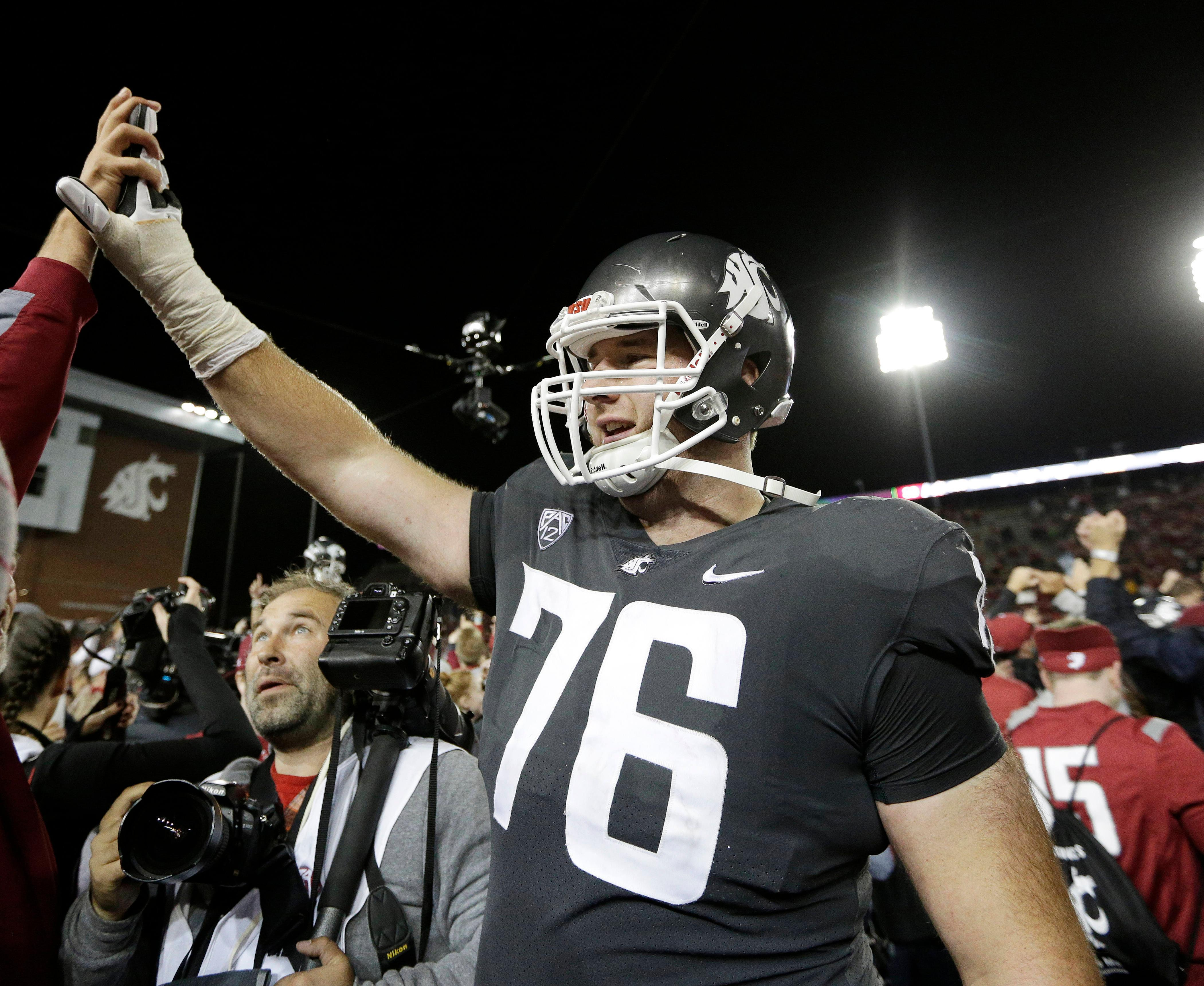 FILE - In this Sept. 29, 2017, file photo, Washington State offensive lineman Cody O'Connell (76) celebrates with fans after his team won an NCAA college football game against Southern California, in Pullman, Wash. O'Connell was selected to the AP All-Conference Pac-12 team announced Thursday, Dec. 7, 2017. (AP Photo/Young Kwak, File)