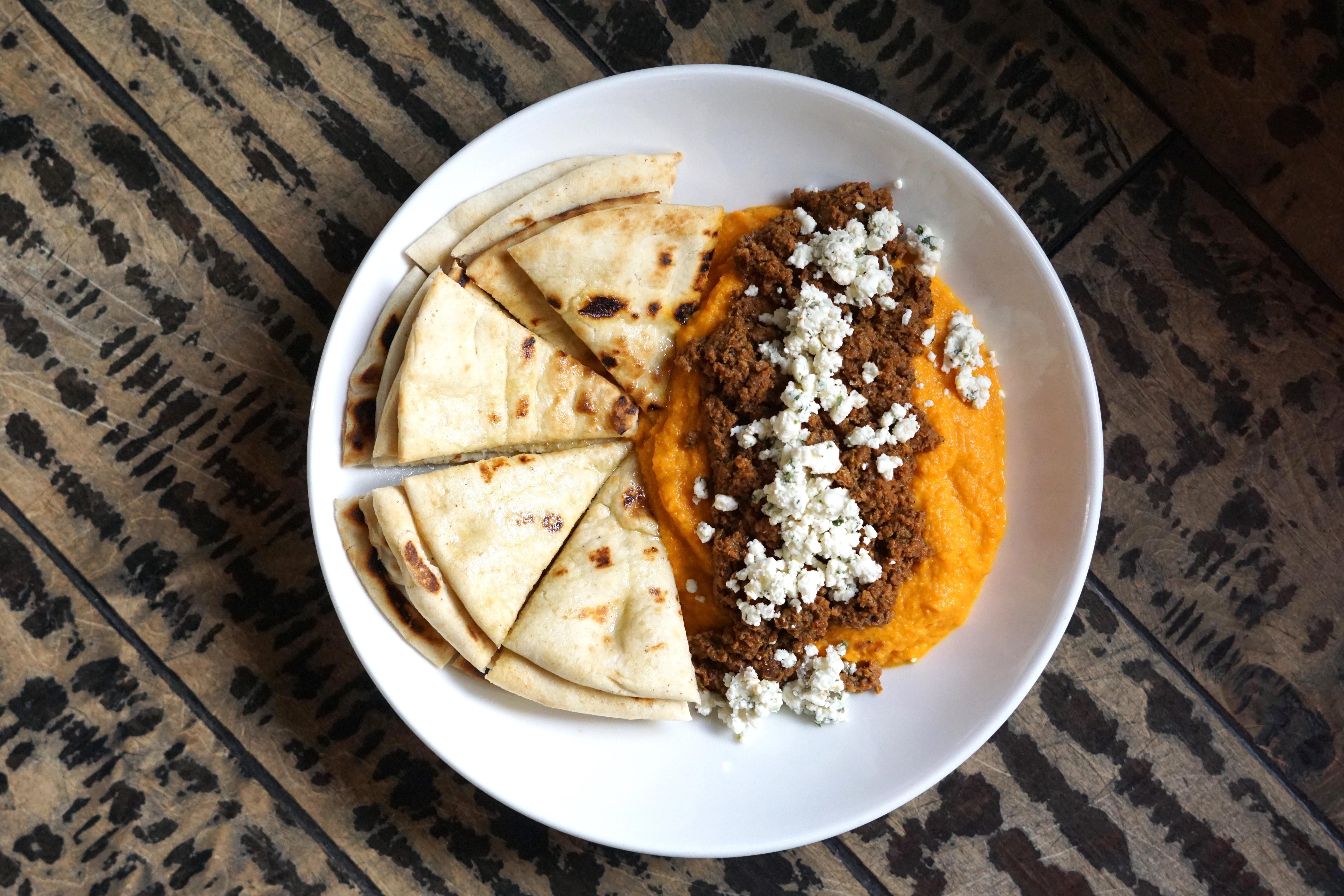 Carrots stand in for chickpeas to create an unconventional hummus. It's topped off with lamb merguez sausage ragu and crumbled feta, and served with grilled pita triangles. (Image: Courtesy Rustico)