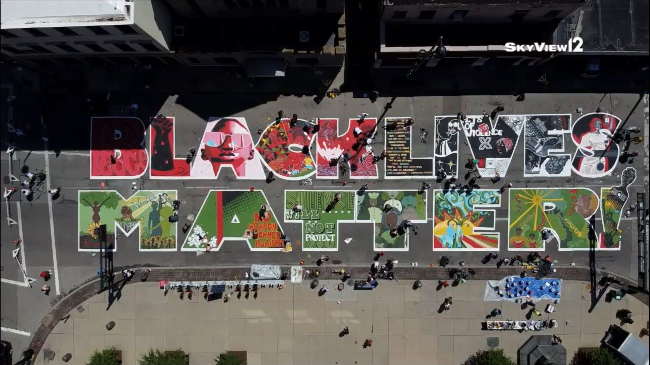 Cincinnati's newest mural isn't on the side of a building; it's on a very important street! Organizers and artists came together during the week to create an enormous Black Lives Matter mural on Plum Street between 8th and 9th Streets. The finished project will reflect the work of 17 black, local artists. The exclamation mark at the end of the mural will feature the work of all 17 artists in one character to signify equality. It was unveiled on June 19th, otherwise known as Juneteenth—a holiday memorializing the final day of slavery in the United States. The project was approved by the mayor and city council. / Image courtesy of Local 12 WKRC's Skyview 12 // Published: 6.19.20