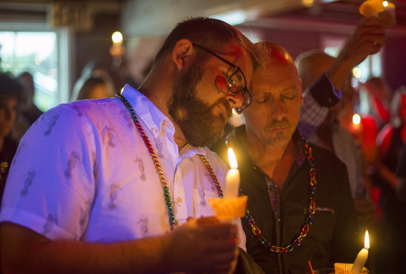 Don Haller, left, and Frank Thompson of Laguna Niguel pray for the victims of Orlando nightclub shooting at Main Street Bar in Laguna Beach, Calif., on Sunday, June 12, 2016. (Kyusung Gong/The Orange County Register via AP)