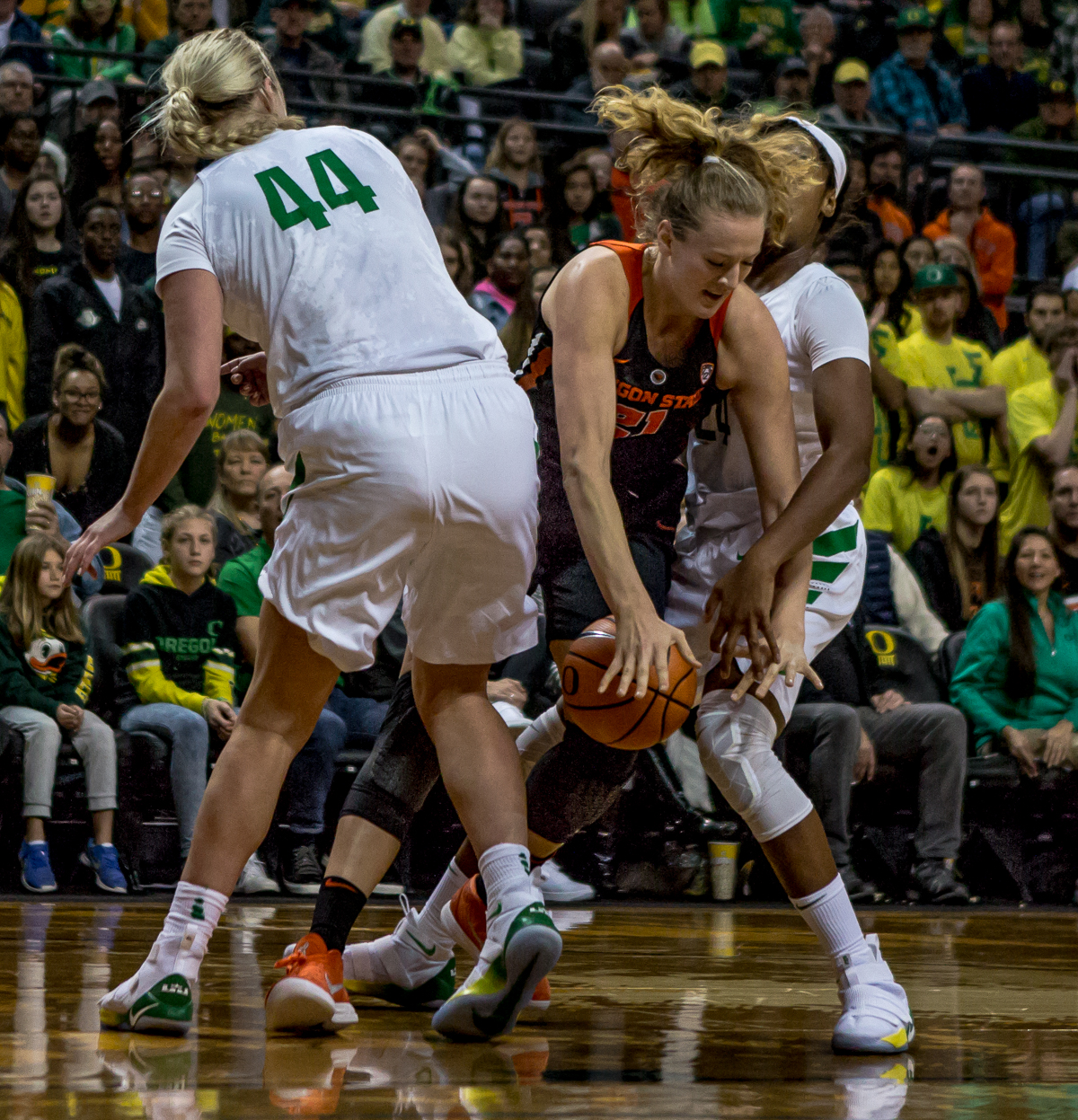 Oregon State center Marie Gülich attempts to push past Oregon forwards Ruthy Hebard (#24) and Mallory McGwire (#44). The Oregon Ducks defeated the Oregon State Beavers 75-63 on Sunday afternoon in front of a crowd of 7,249 at Matthew Knight Arena. The Ducks and Beavers split the two game Civil War with the Beavers defeating the Ducks on Friday night in Corvallis. The Ducks had four players in double digits: Satou Sabally with 21 points, Maite Cazorla with 16, Sabrina Ionescu with 15, and Mallory McGwire with 14. The Ducks shot 48.4% from the floor compared to the Beavers 37.3%. The Ducks are now 7-1 in conference play. Photo by Ben Lonergan, Oregon News Lab