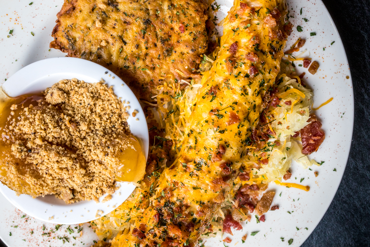 Bier Cheese Mettwurst: breaded mettwurst served on a bed of sauerkraut, smothered in haus-made bier cheese, cheddar cheese, and bacon served with a potato pancake and caramelized apples / Image: Catherine Viox // Published: 8.10.20