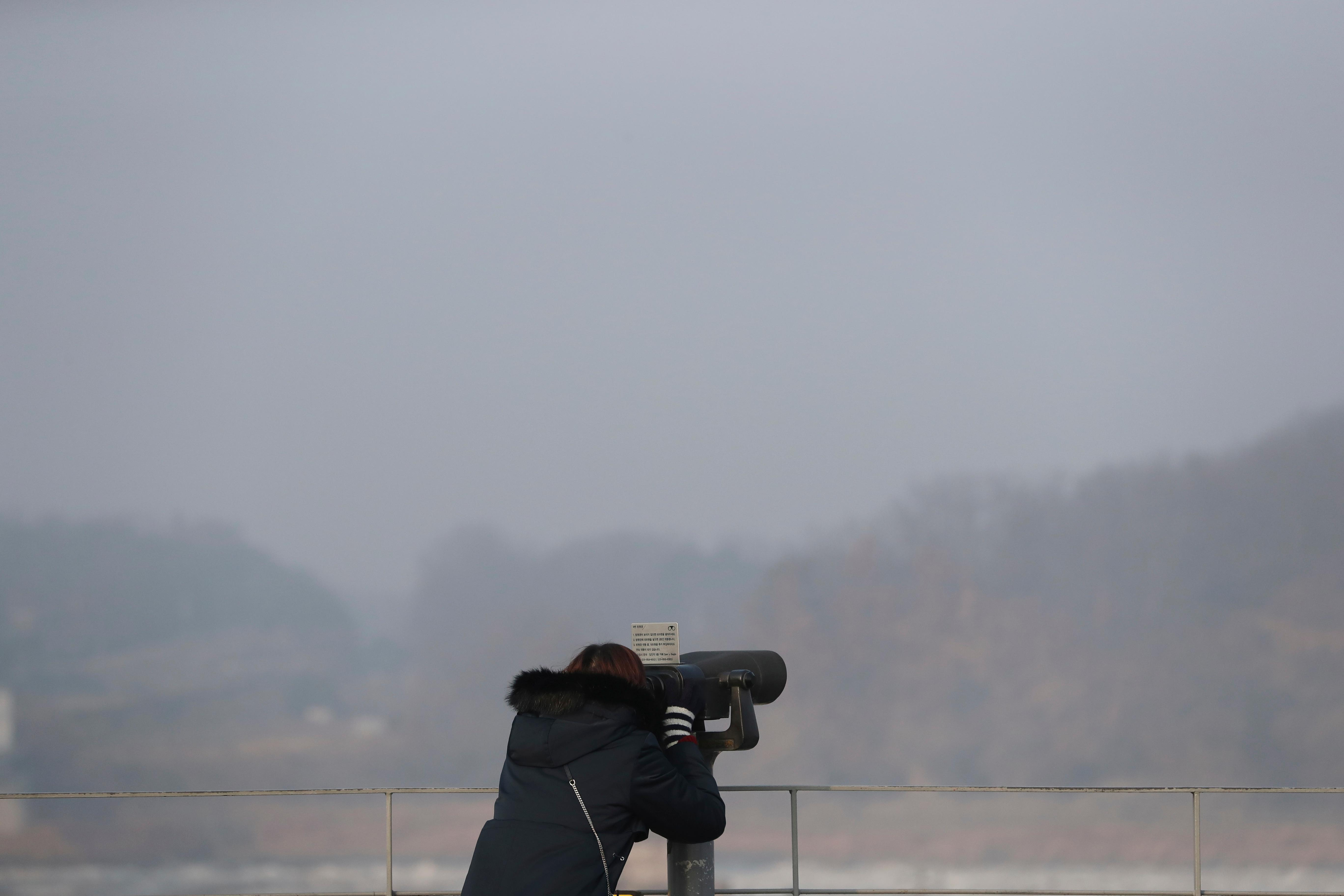 A visitor uses binoculars to see the north side at the Imjingak Pavilion in Paju, South Korea, Wednesday, Jan. 17, 2018. The two Koreas are meeting Wednesday for the third time in about 10 days to continue their discussions on Olympics cooperation, days ahead of talks with the IOC on North Korean participation in the upcoming Winter Games in the South. (AP Photo/Lee Jin-man)