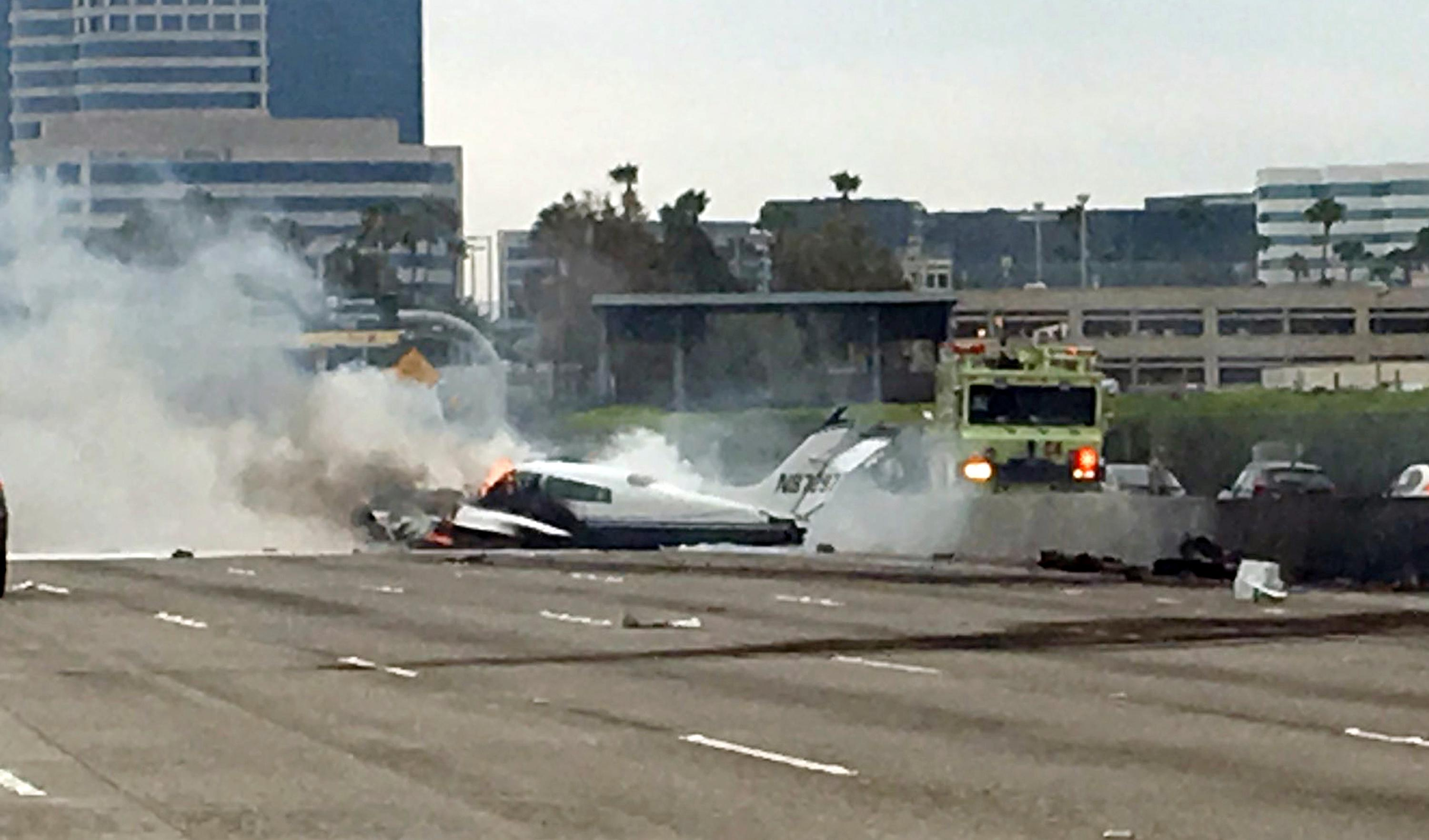 Flame and smoke erupt from a twin-engine prop jet after it crashed on Interstate 405, just short of the runway at John Wayne Orange County Airport, in Costa Mesa, Calif., Friday, June 30, 2017. Officials said two people have been injured and will be taken by helicopter to a hospital. The freeway was shut down in both directions. (Rafi Mamalian via AP)
