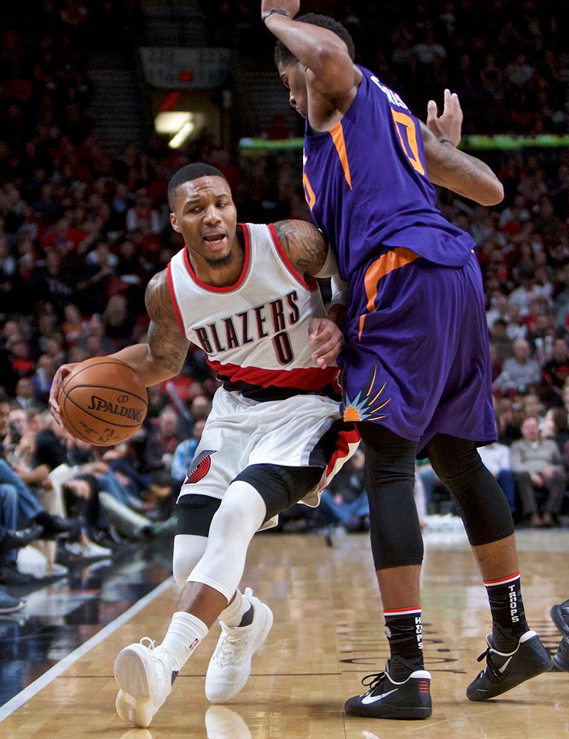 Portland Trail Blazers guard Damian Lillard, left, is fouled by Phoenix Suns forward Marquese Chriss during the first half of an NBA basketball game in Portland, Ore., Tuesday, Nov. 8, 2016. (AP Photo/Craig Mitchelldyer)