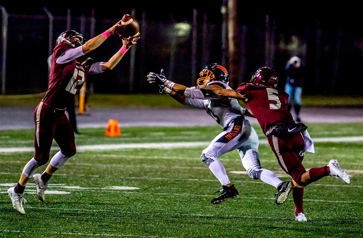 Willamette's Griffin LaVassaur (#12) makes the interception against Roseburg. The Roseburg Indians defeated the Willamette Wolverines 21-20 at Willamette on Friday. Photo by August Frank, Oregon News Lab