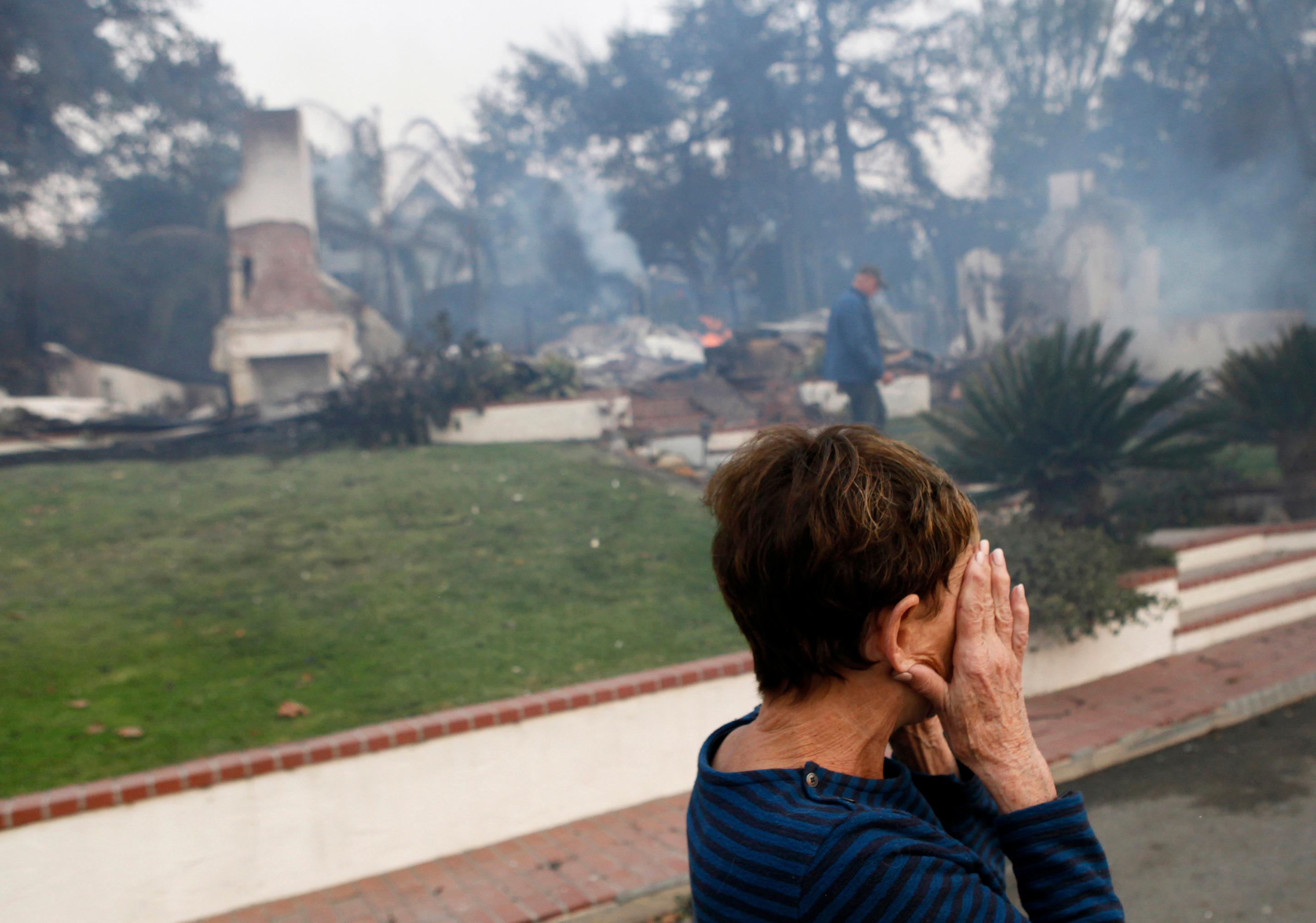 A woman cries as she covers her face near her destroyed home a wildfire swept through Ventura, Calif., Tuesday, Dec. 5, 2017. (Daniel Dreifuss via AP)