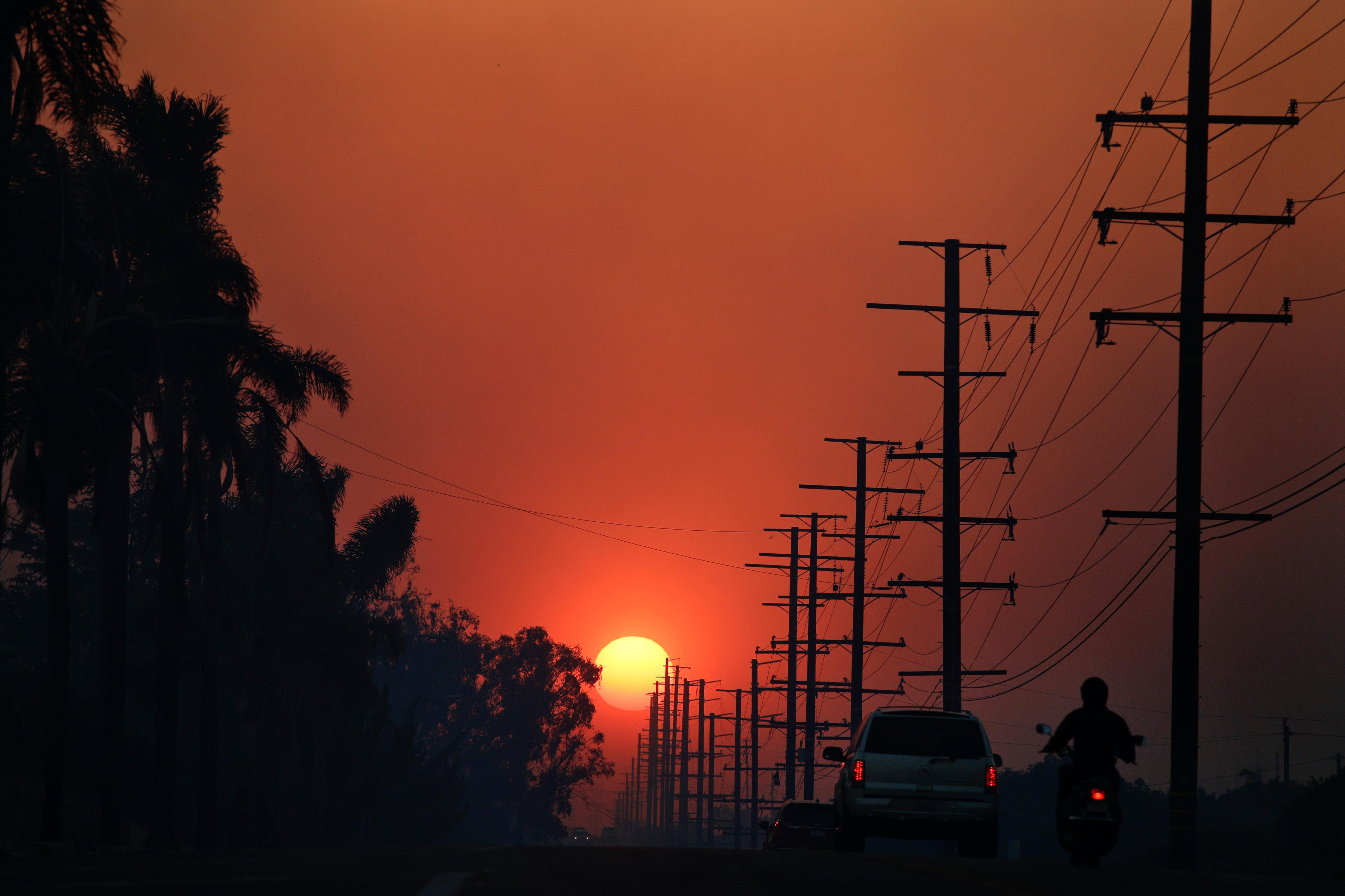 The sun is seen through thick smoke generated by a wildfire Tuesday, Dec. 5, 2017, in Santa Paula, Calif. Raked by ferocious Santa Ana winds, explosive wildfires northwest of Los Angeles and in the city's foothills burned a psychiatric hospital and scores of homes and other structures Tuesday and forced the evacuation of tens of thousands of people. (AP Photo/Jae C. Hong)
