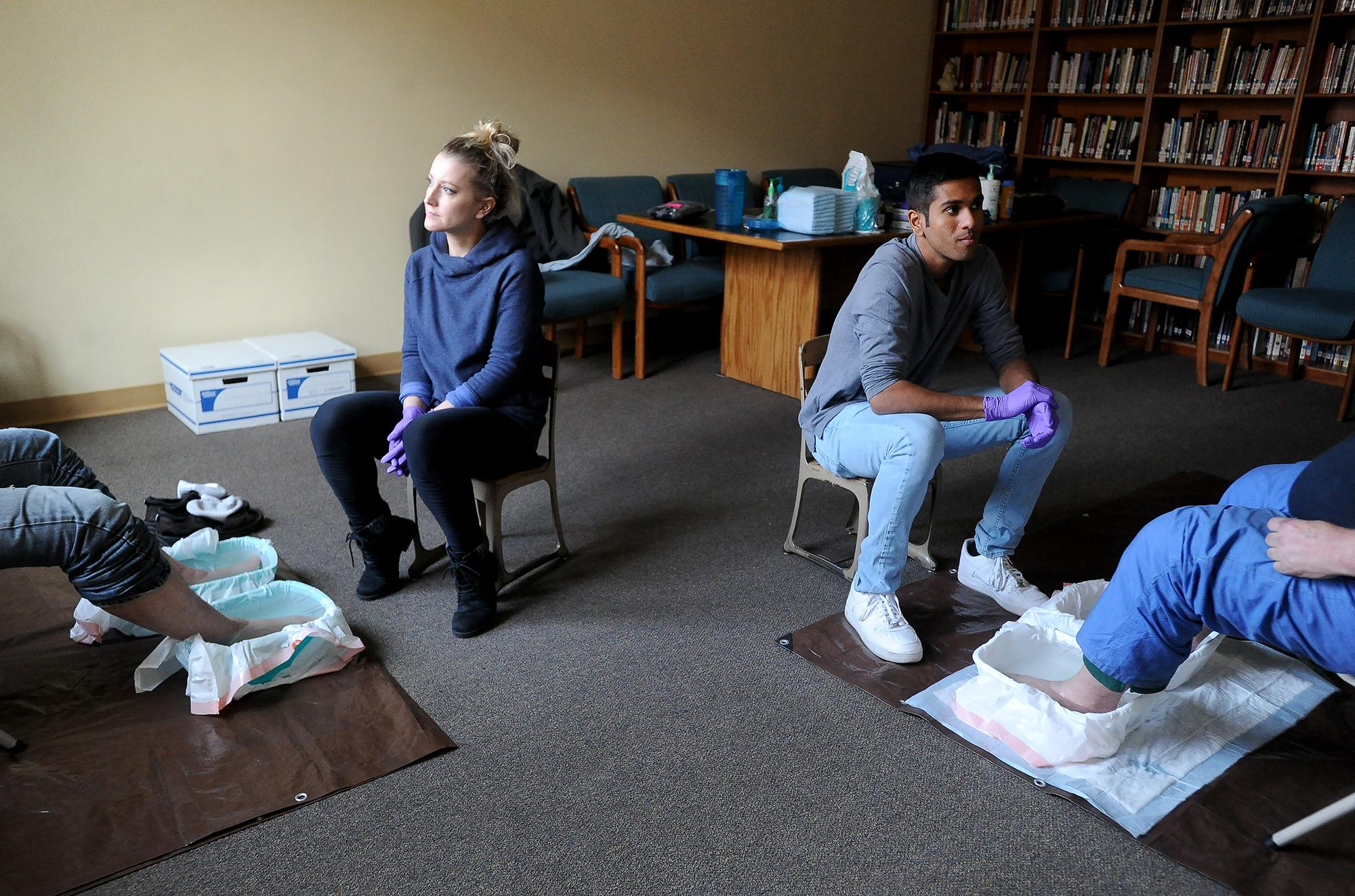 Oregon Health and Sciences University nursing students Ashley Higinbotham and Asish Kumar listen as their homeless clients share stories about their day as their feet are soaked and washed at the First United Methodist Church in Ashland. Photo by Denise Baratta