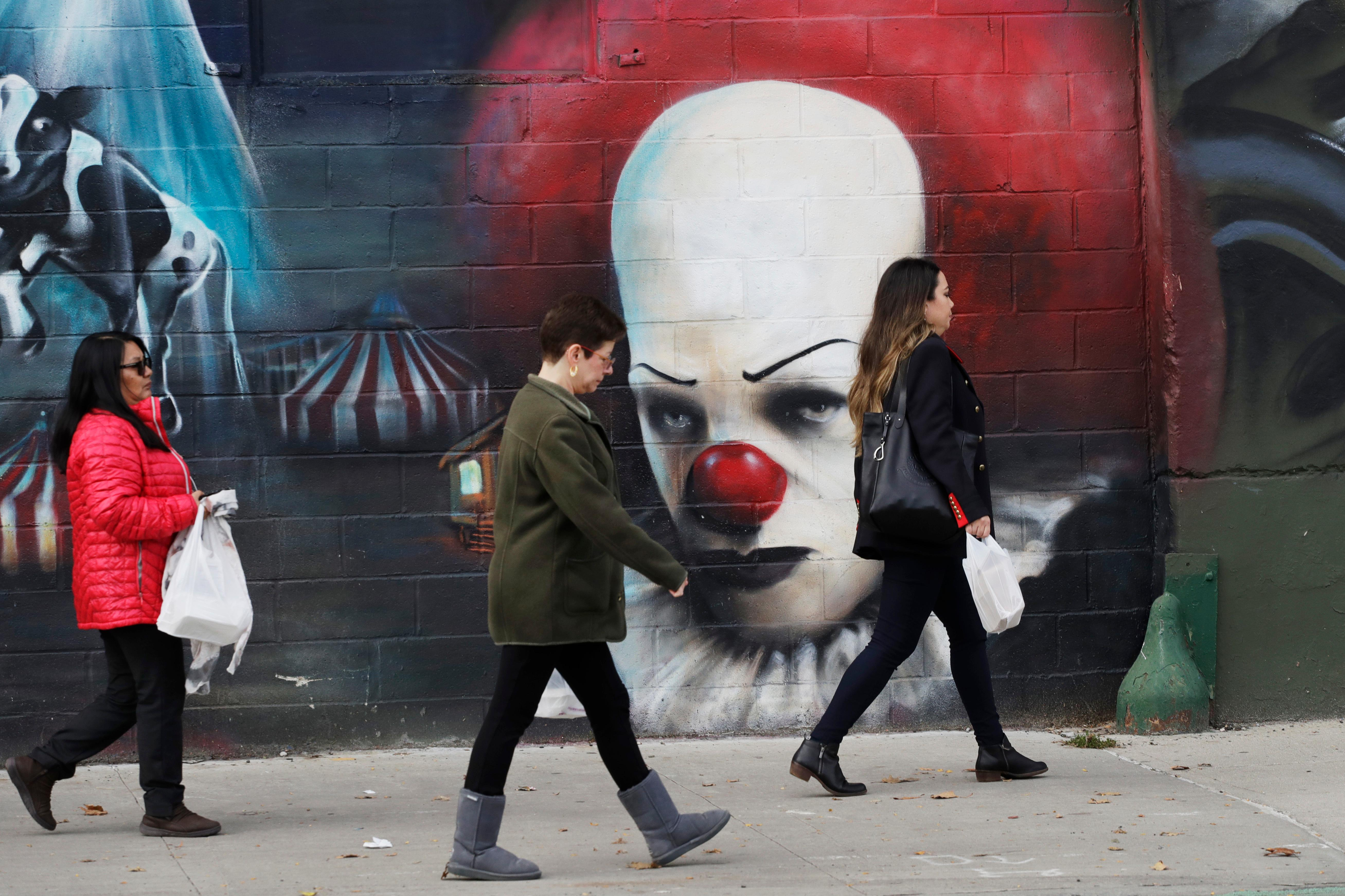 In this Wednesday, Nov. 7, 2018, photo, people walk past a mural in Long Island City in the Queens borough of New York. (AP Photo/Mark Lennihan)