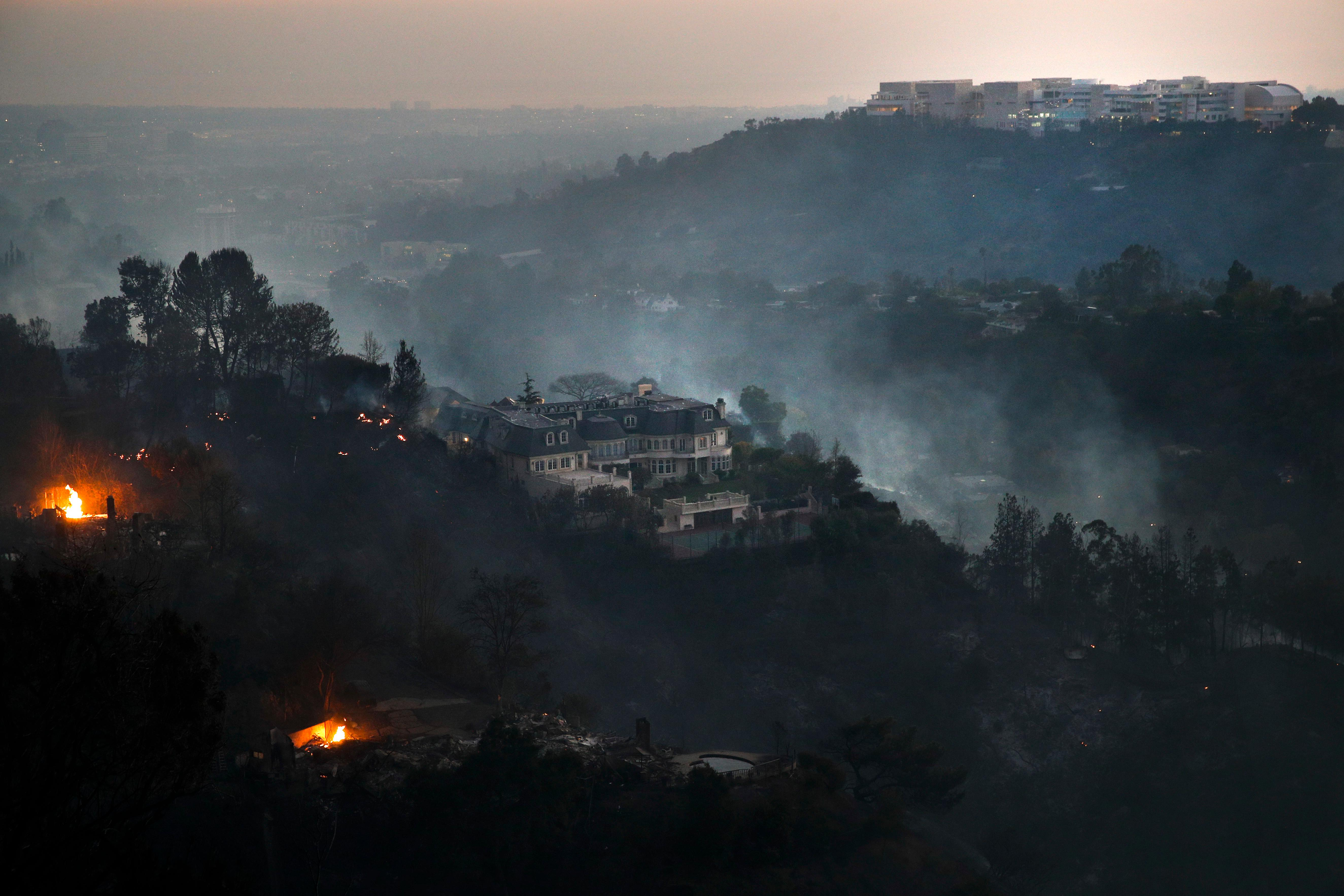 A mansion that survived a wildfire sits on a hilltop as the Getty Center, top right, is visible in distance in the Bel Air district of Los Angeles Wednesday, Dec. 6, 2017. A dangerous new wildfire erupted in the tony Bel Air area of Los Angeles early Wednesday as firefighters battled three other destructive blazes across Southern California. (AP Photo/Jae C. Hong)