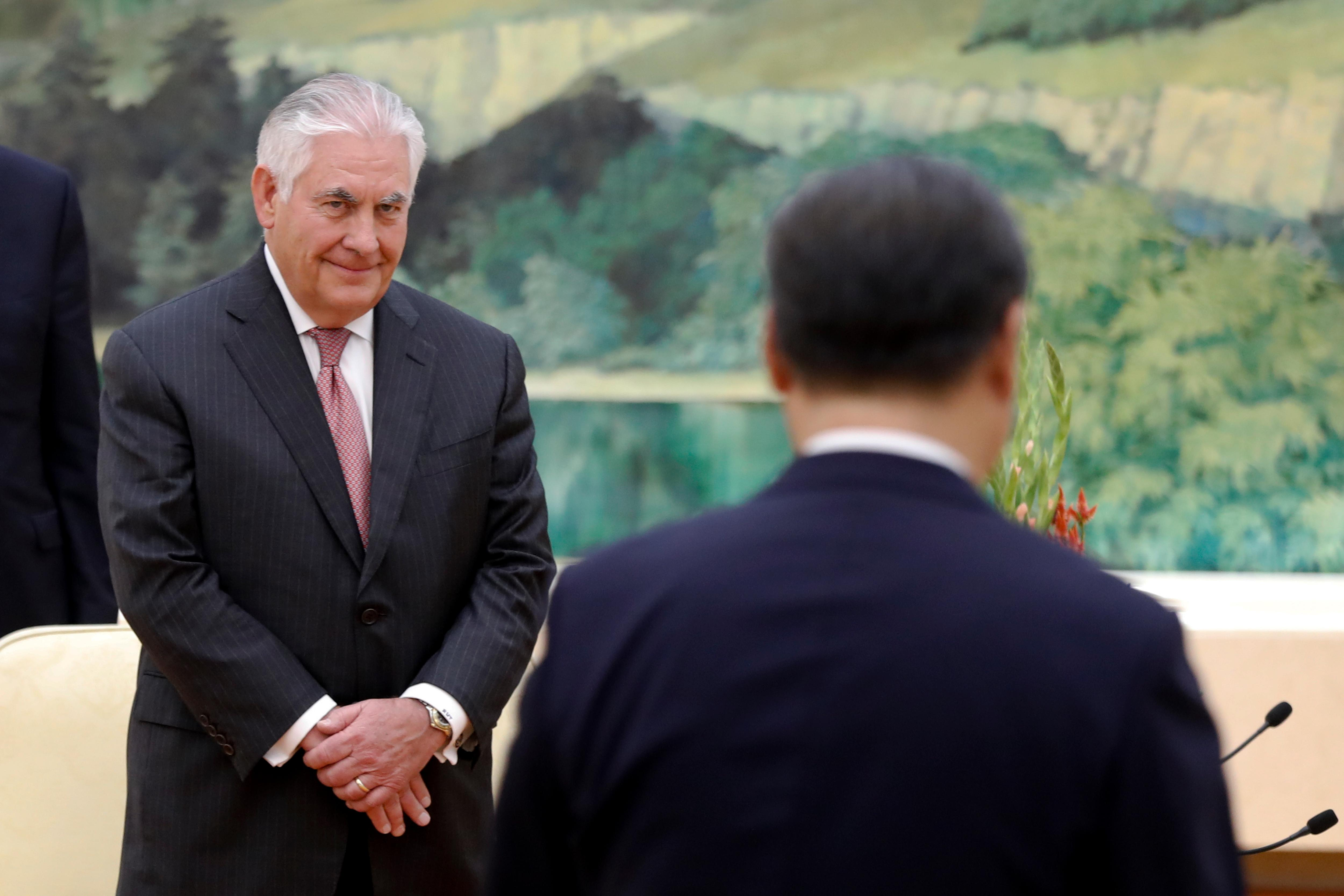U.S. Secretary of State Rex Tillerson, left, looks at China's President Xi Jinping walks to his seat during a meeting at the Great Hall of the People in Beijing, Saturday, Sept. 30, 2017. (AP Photo/Andy Wong, Pool)