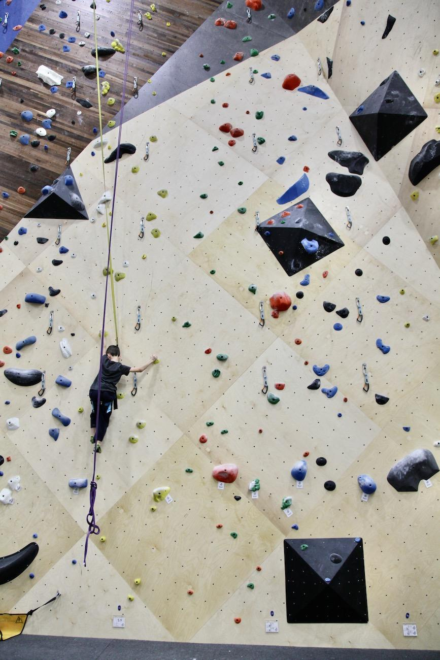 Almost lost in the array of some of the gym's 15,000 climbing holds, a young climber moves his way up a beginner route, aided by an autobelay device. Normally a partner would belay a climber, but autobelay devices eliminate the need for a human belayer. / Image: Chez Chesak // Published: 2.1.20