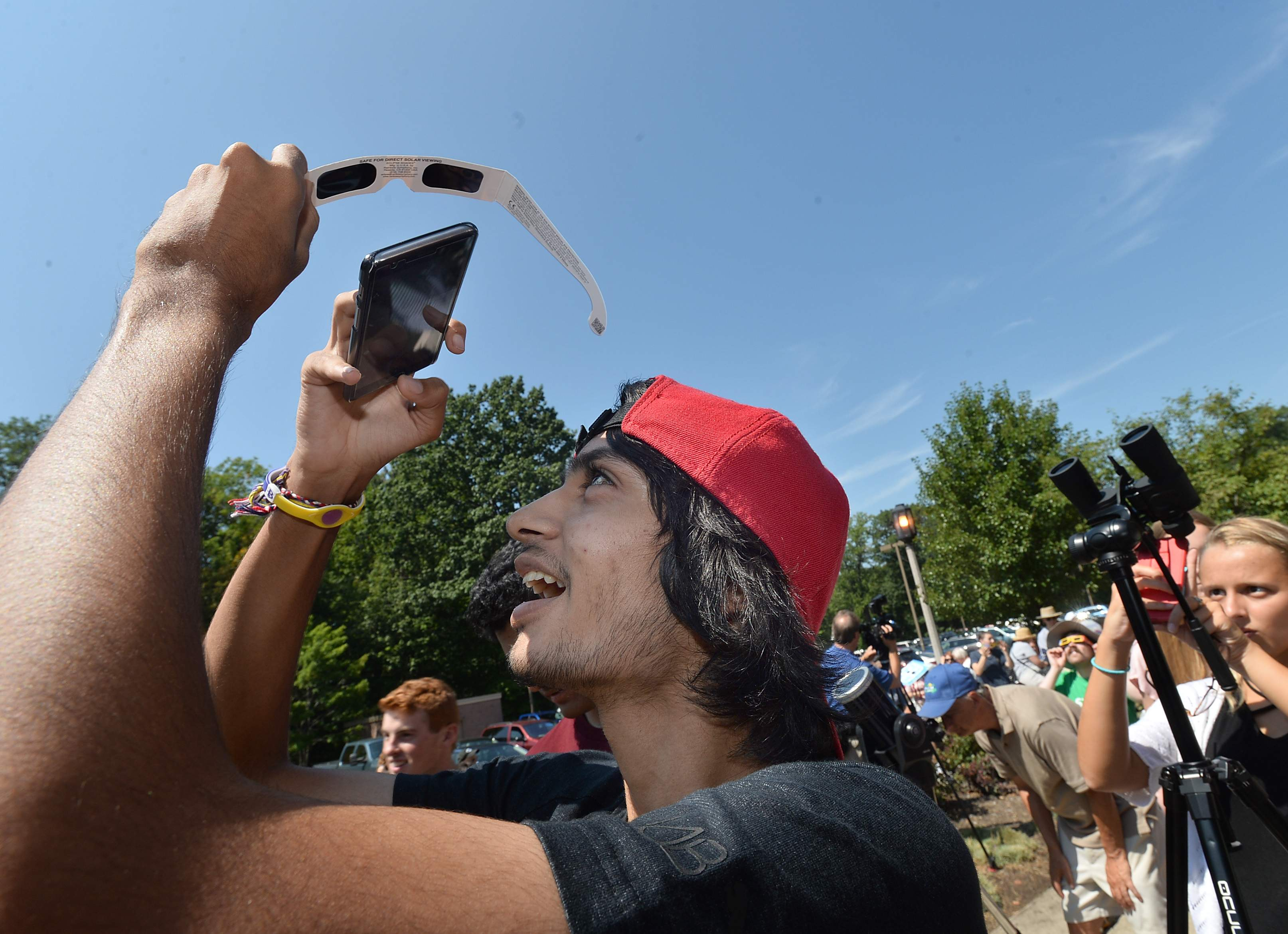 Swaraj Patel, 18, takes a photo of the eclipse on his smartphone through a pair of solar glasses Aug. 21 at an eclipse-viewing party held at Penn State Behrend in Harborcreek Township. Patel is a sophomore computer engineering student from India. Hundreds turned out for the event at Behrend, which featured telescopes fitted with solar filters available for viewing the partial eclipse. [CHRISTOPHER MILLETTE/ERIE TIMES-NEWS]
