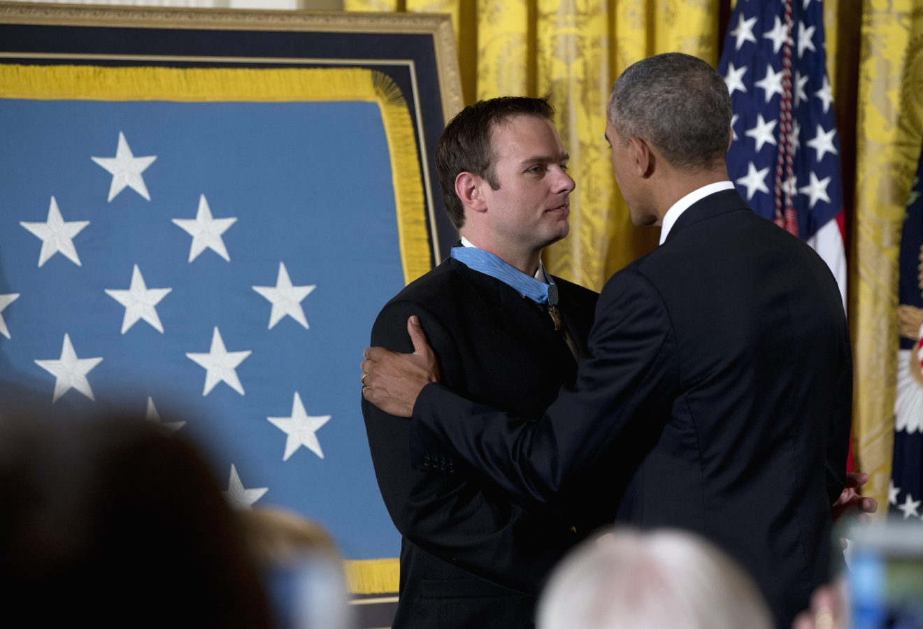 President Barack Obama talks to Senior Chief Special Warfare Operator Edward Byers  after presenting him with the Medal of Honor during a ceremony in the East Room of the White House in Washington, Monday, Feb. 29, 2016. U.S. Navy. Senior Chief Byers received the Medal of Honor for his courageous actions while serving as part of a team that rescued an American civilian being held hostage in Afghanistan on December 8-9, 2012. (AP Photo/Carolyn Kaster)