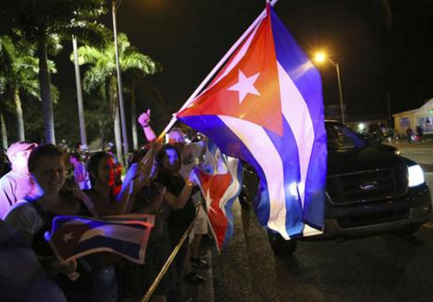 The Cuban community celebrates the announcement that Fidel Castro died as they gather in front La Carreta Restaurant, early Saturday, Nov. 26, 2016, in Miami. Within half an hour of the Cuban government's official announcement that former President Fidel Castro had died, Friday, Nov. 25, 2016, at age 90, Miami's Little Havana teemed with life - and cheers. (David Santiago/El Nuevo Herald via AP)