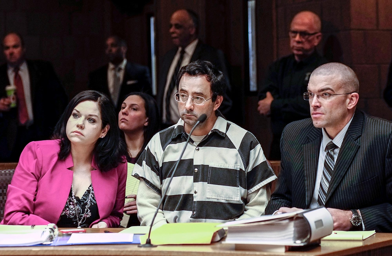 Dr. Larry Nassar, center, and his attorneys, Shannon Smith and Matt Newburg, listen to Judge Donald Allen Jr. rule that Nassar, a former Michigan State University and USA Gymnastics sports doctor, should stand trial on sexual assault charges during a hearing, Friday, Feb. 17, 2017, in Lansing, Mich. Nassar is accused of assaulting a girl from the age of 6 until the girl was 12 at his home in Holt, Mich. He's pleaded not guilty. (Robert Killips/Lansing State Journal via AP)