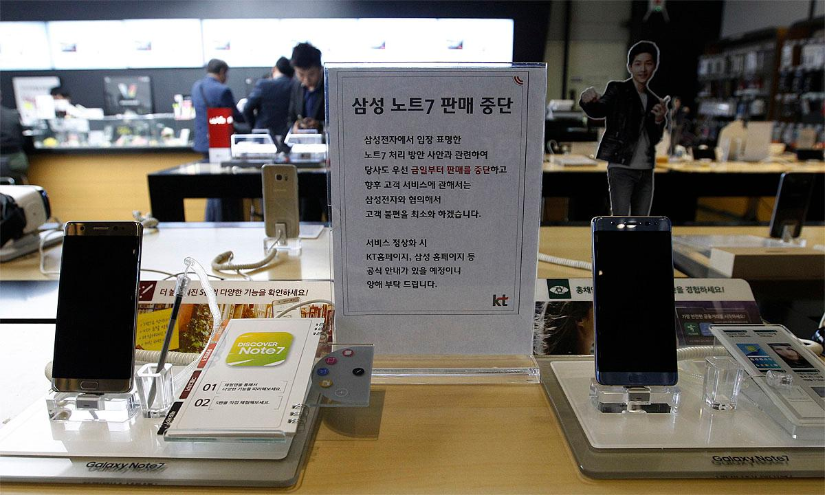 "Powered-off Samsung Electronics Galaxy Note 7 smartphones are displayed at a mobile phone shop in Seoul, South Korea, Tuesday, Oct. 11, 2016. Samsung Electronics said Tuesday that it is ending the Galaxy Note 7 smartphone production permanently, a day after it halted global sales of the star-crossed devices. The letters on the sign read ""We halt selling Samsung Electronics Galaxy Note 7 smartphones."" (AP Photo/Ahn Young-joon)"