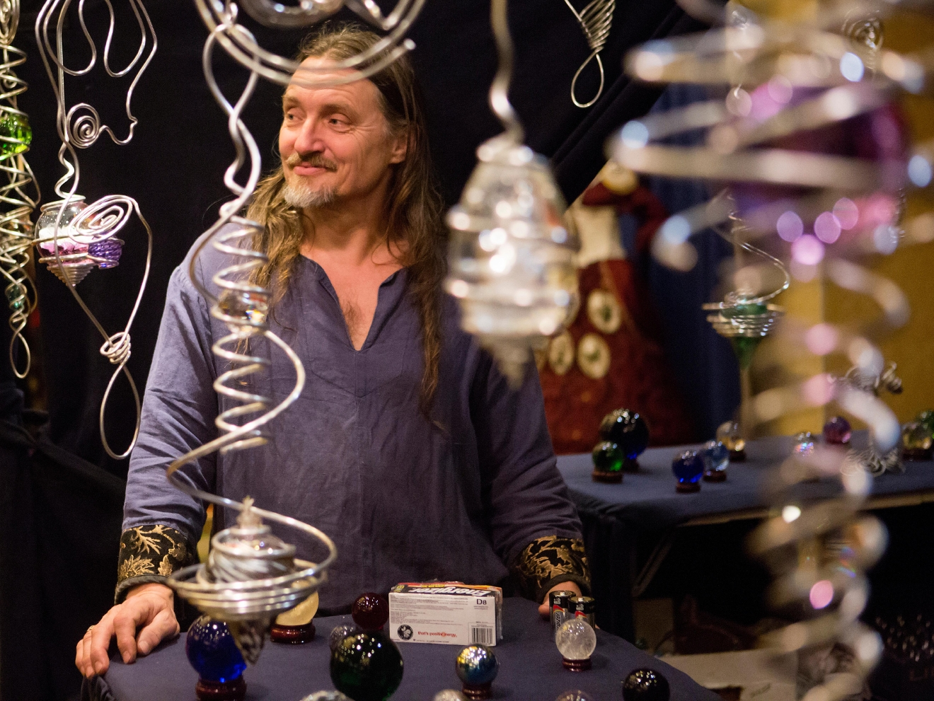 Spiral Alchemist Amaru stands behind his artwork in his booth at Mythicworlds Convention and Masquerades. (Sy Bean / Seattle Refined)