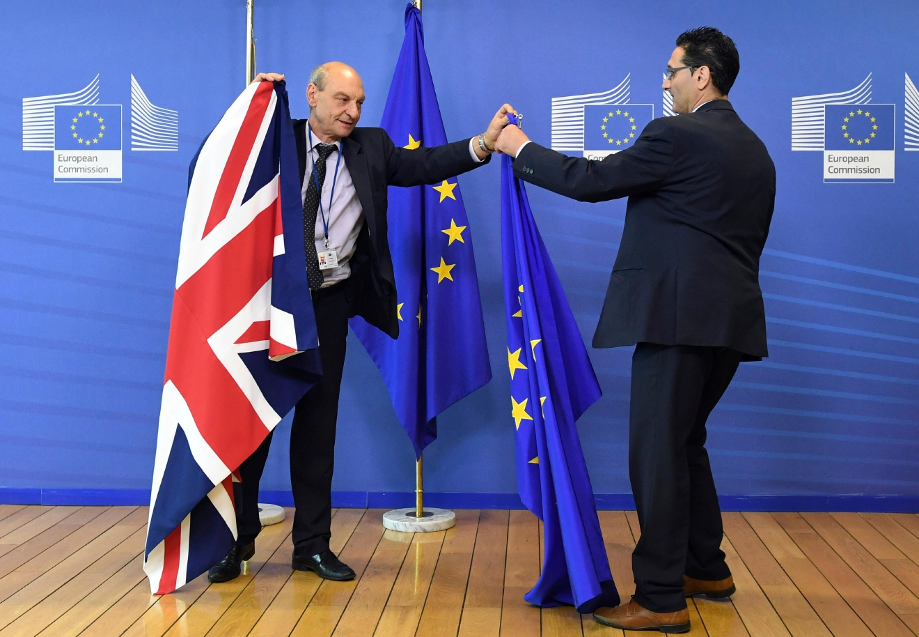 FILE - In this June 28, 2016 file photo, members of protocol adjust the British and EU flags at EU headquarters in Brussels. On Monday, March 20, 2017 the European Commission said it has been informed in advance of Britain's plans to trigger its exit from the EU on March 29 and stands ready to help launch the negotiations. (AP Photo/Geert Vanden Wijngaert, File)