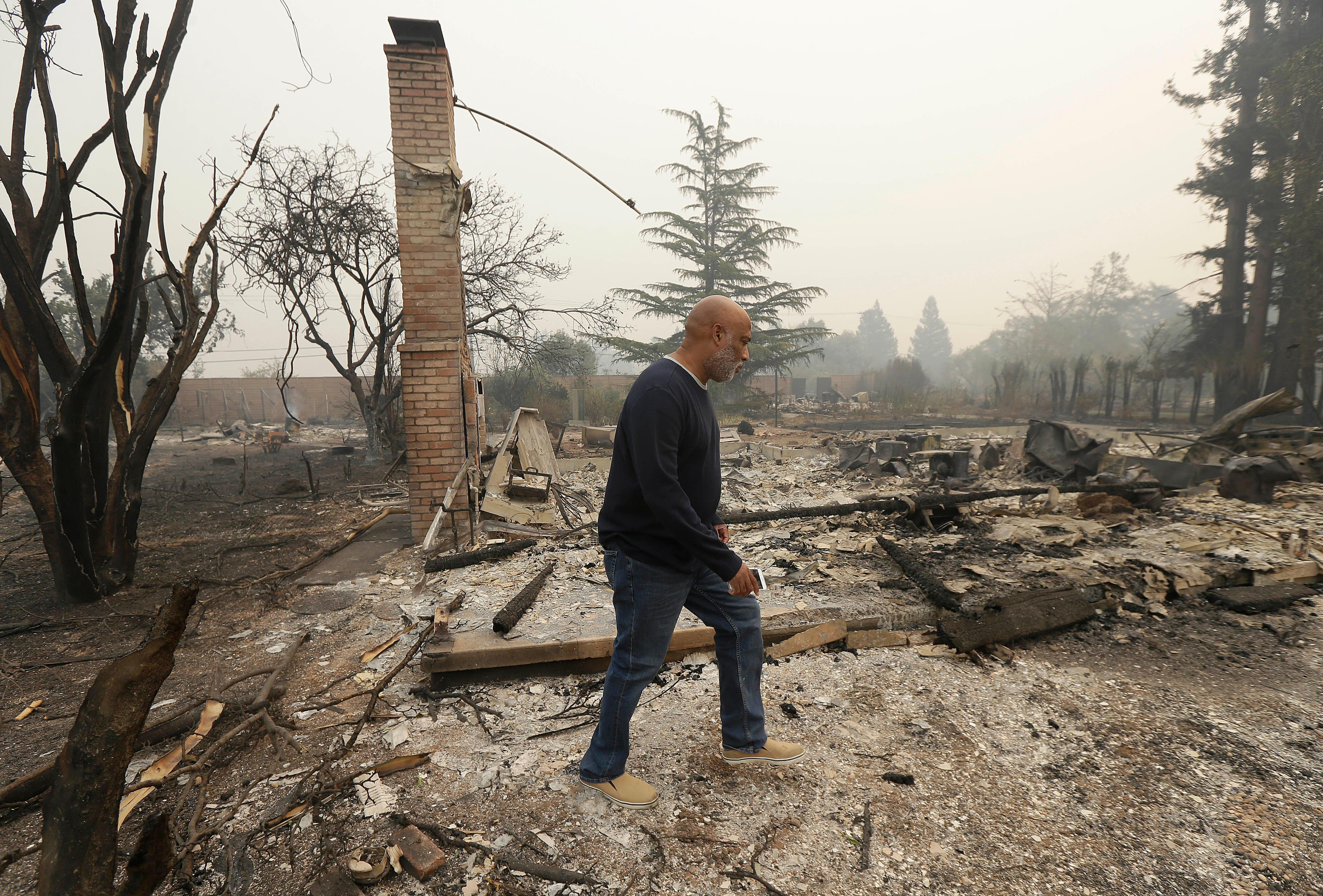 Darrel Spain walks through the remains of his house destroyed from fires as he and his husband look for their missing cat in Kenwood, Calif., Tuesday, Oct. 10, 2017. (AP Photo/Jeff Chiu)