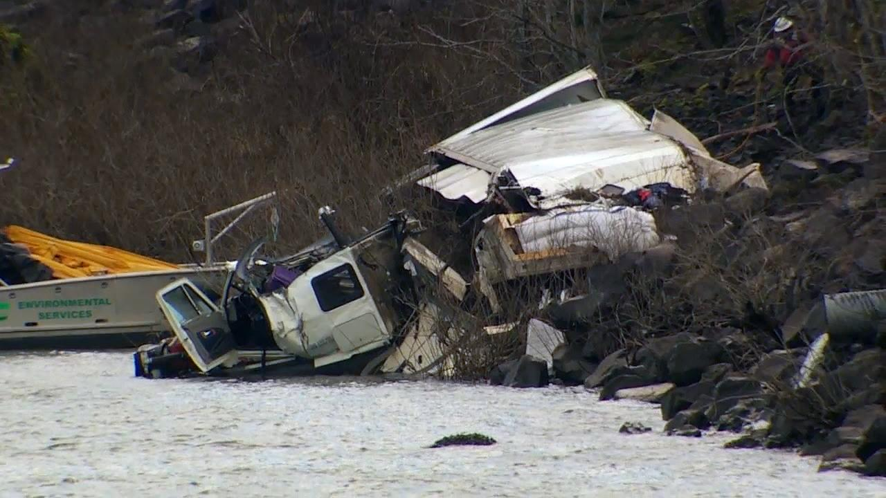 The battered remains of a tractor-trailer lay partially submerged in the Columbia River Tuesday. On Monday evening it crashed through a guardrail on Interstate 84 and down an embankment. No one was seriously hurt. (KATU Photo)