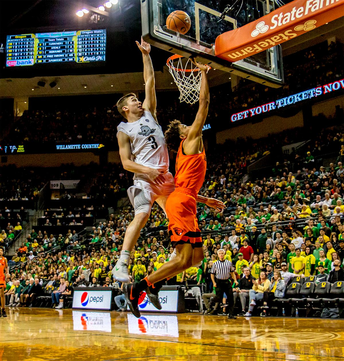 The Beaver's Stephen Thompson Jr. (#1) goes up for the basket as the Duck's Payton Pritchard (#3) attempts to defend the basket. The Ducks defeated the Beavers in the civil war game, 66-57, at Matthew Knight Arena on Saturday night. Elijah Brown scored a game high of 20 points with 18 of the points coming in the first half, Paul White added 17 points. The Ducks are now 14-7 overall and 4-4 in conference play. The Ducks will next face California on Thursday Feb. 1 at 6:00 p.m. Photo by August Frank, Oregon News Lab