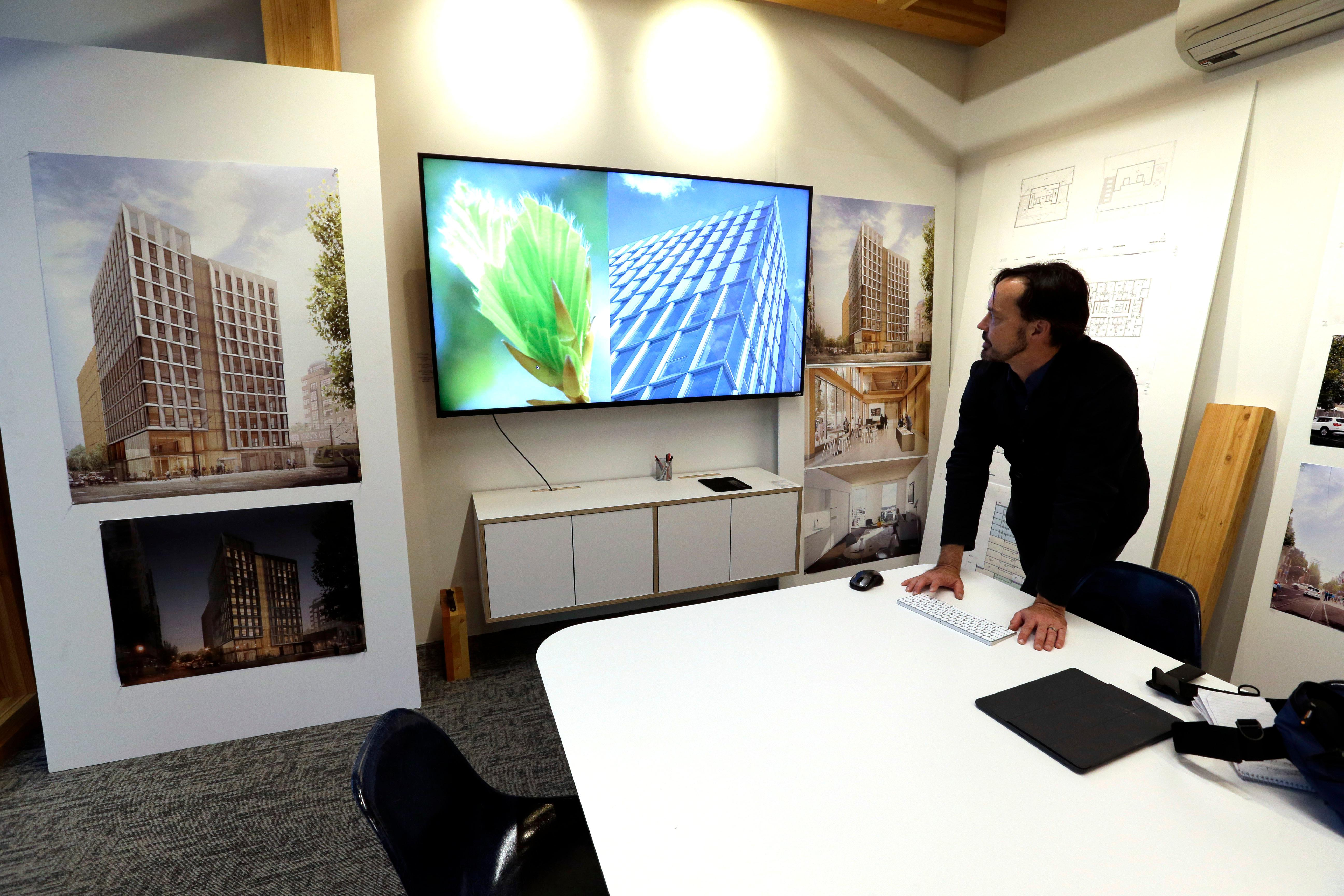 FILE- In this Nov. 15, 2016, file photo, Lever Architecture founder Thomas Robinson looks over artist renderings in Portland, Ore., of a 12-story all-wood building that his firm is working on to be built in Portland's trendy Pearl District. City officials in Portland have approved a construction permit for the first all-wood high-rise building in the nation. Developers announcing the approval Tuesday, June 6, 2017, say it's a milestone for wood technology. (AP Photo/Don Ryan, File)