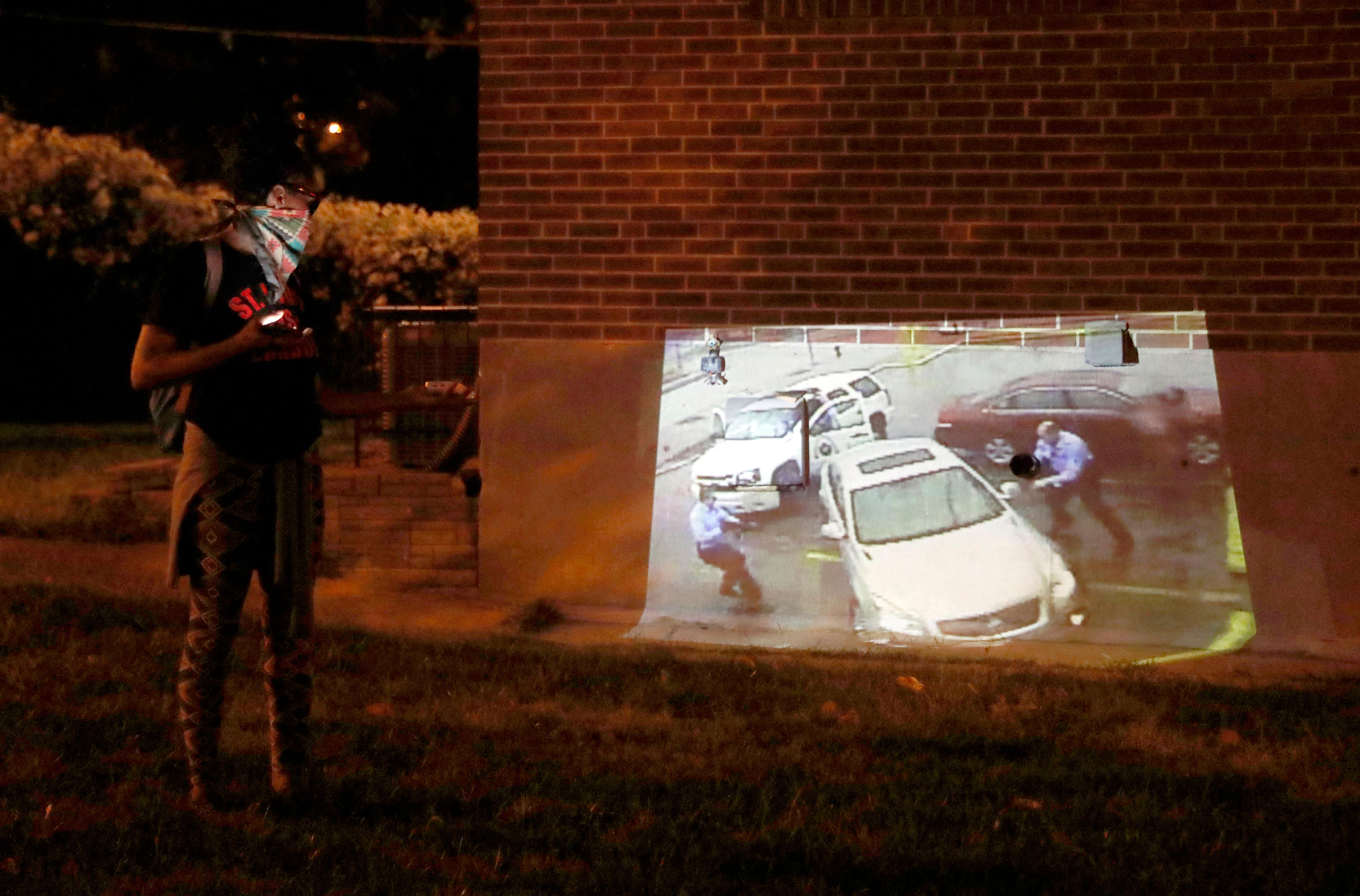 A protester uses a small projector to project images on a house while marching in response to a not guilty verdict in the trial of former St. Louis police officer Jason Stockley Saturday, Sept. 16, 2017, in St. Louis. Stockley was acquitted in the 2011 killing of a black man following a high-speed chase. (AP Photo/Jeff Roberson)