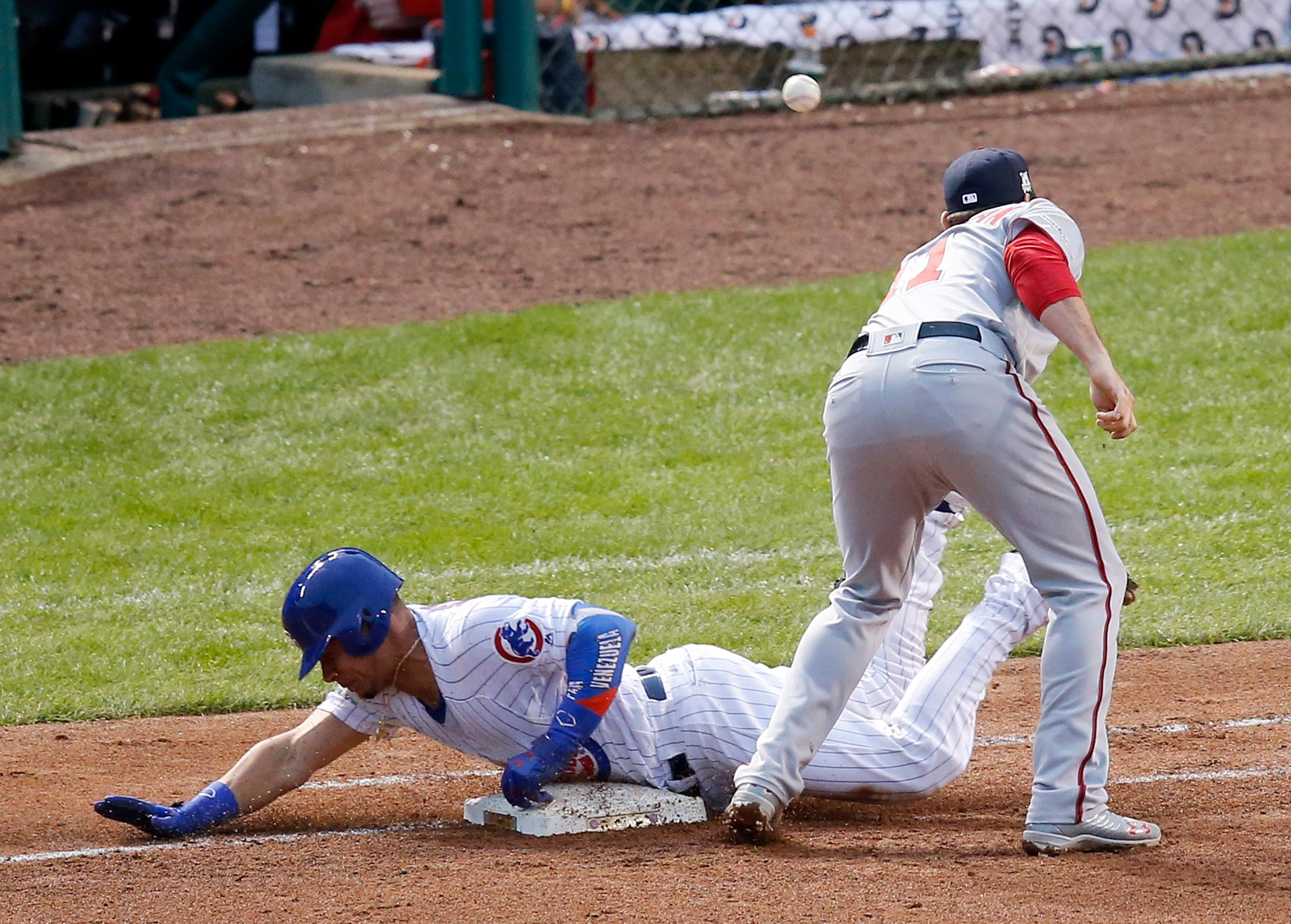 Chicago Cubs' Willson Contreras slides safely to first against Washington Nationals first baseman Ryan Zimmerman (11) and advances to second on a throwing error by Washington Nationals pitcher Stephen Strasburg during the fourth inning of Game 4 of baseball's National League Division Series, Wednesday, Oct. 11, 2017, in Chicago. (AP Photo/Charles Rex Arbogast)