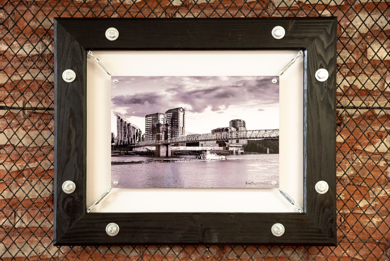 A black and white metallic print of the Ohio River looking toward Newport, KY, suspended within a frame constructed by Ryan Hill of ImageNationS Photography{ }/ Image: Melissa Sliney // Published: 6.26.19