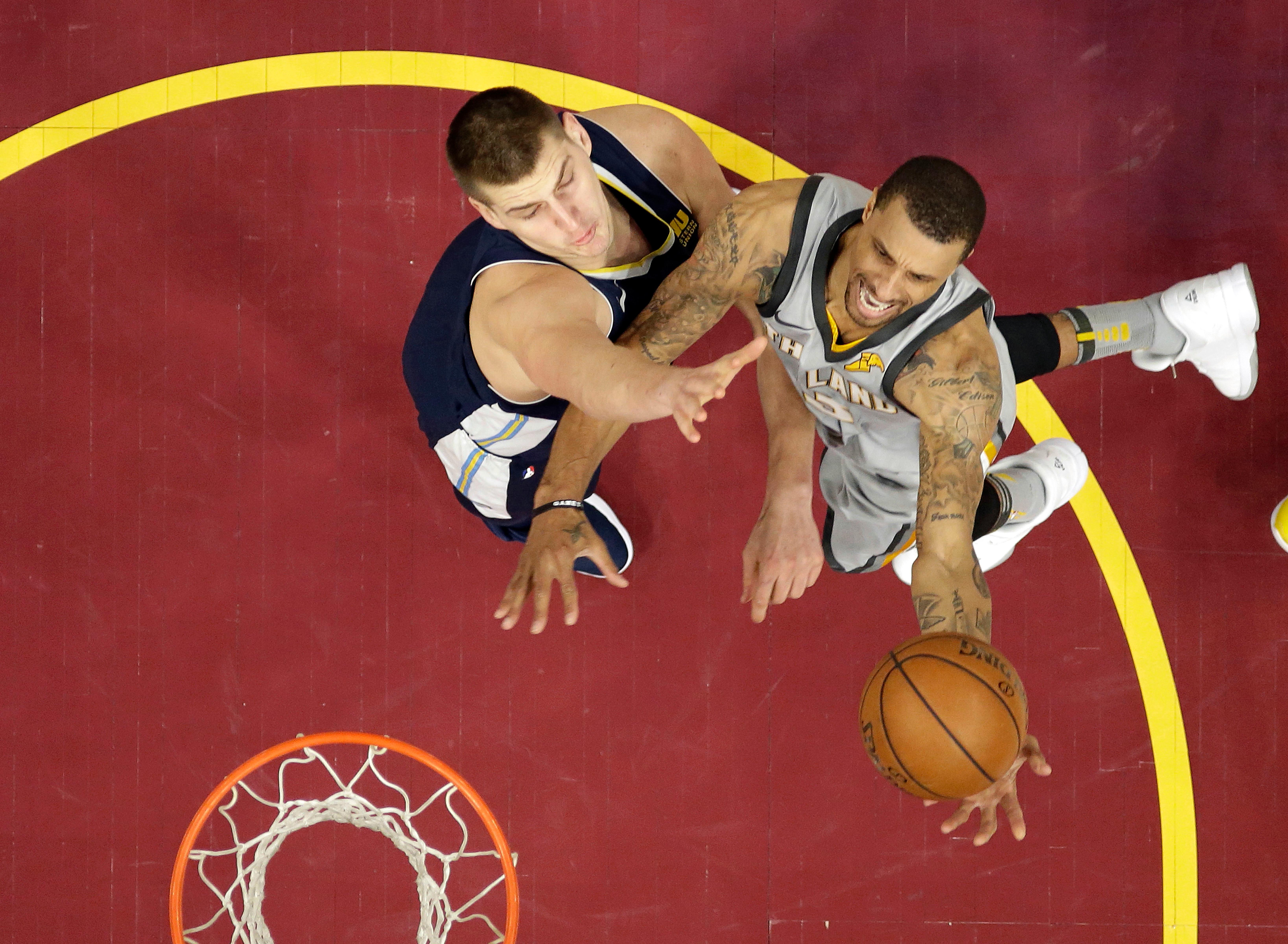 Cleveland Cavaliers' George Hill, right, drives to the basket against Denver Nuggets' Nikola Jokic, from Serbia, in the first half of an NBA basketball game, Saturday, March 3, 2018, in Cleveland. (AP Photo/Tony Dejak)