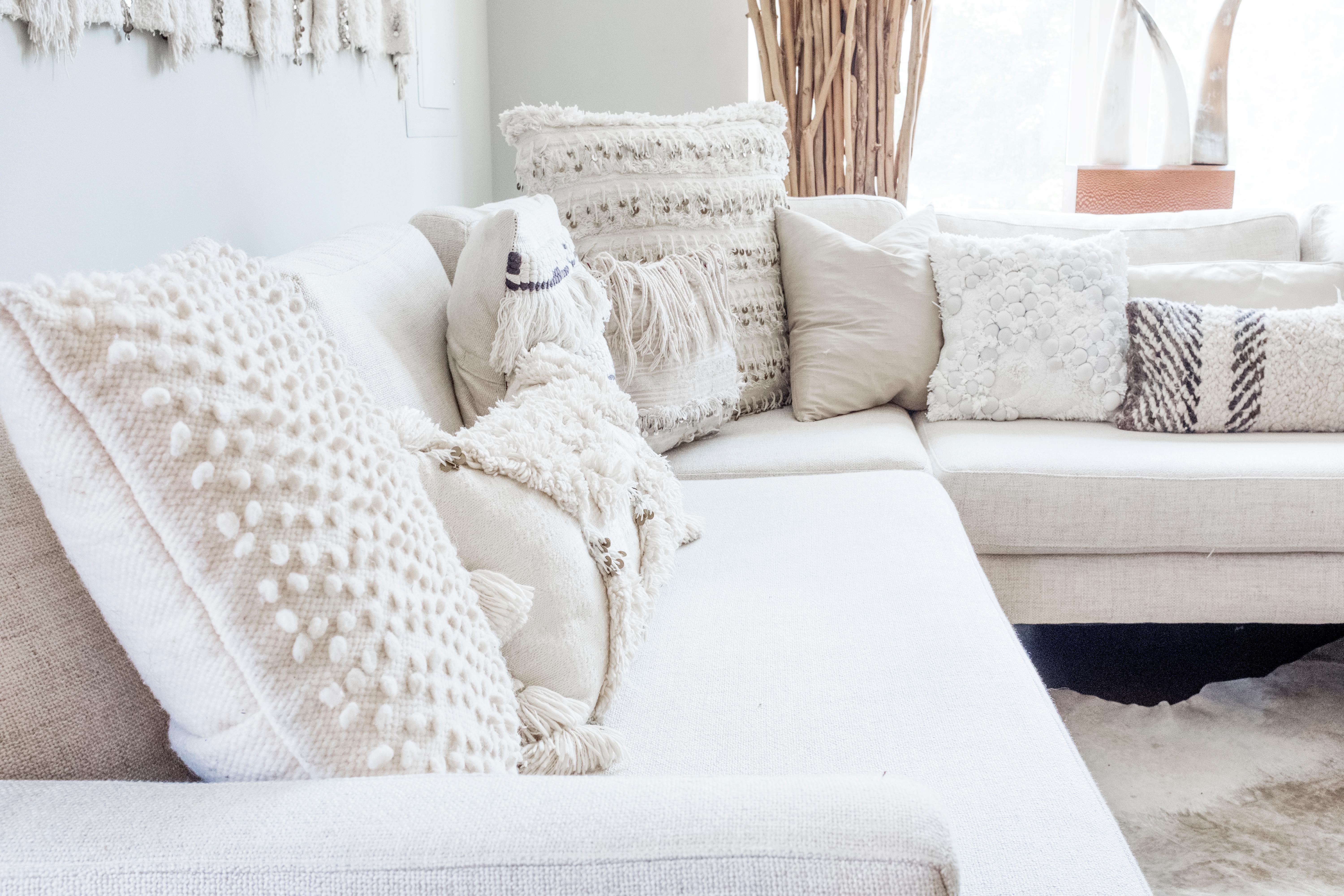 For a really bold look to really transform your room, pick a single color scheme (such as white) and then cover your whole couch with pillows in that hue, but of various sizes and textures. (Image: Ashley Hafstead)