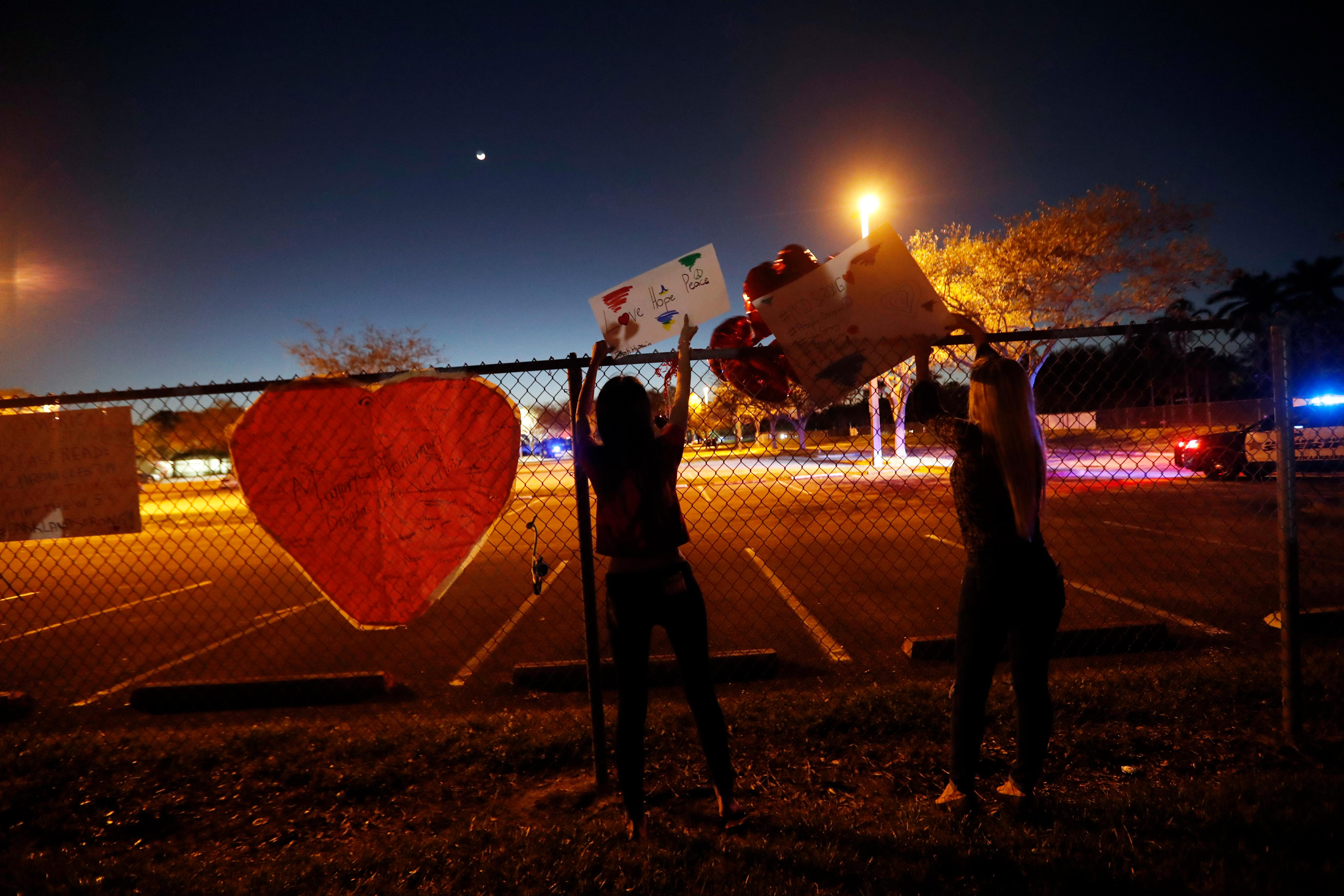 Nyla Hussain, 16, a student at Marjory Stoneman Douglas High School, hangs signs on the fence of the school with her mother Heather Hussain, right, in Parkland, Fla., Sunday, Feb. 18, 2018. Nikolas Cruz, a former student, carried out a mass shooting, killing 17 students and faculty on Wednesday, and was charged with 17 counts of premeditated murder on Thursday. (AP Photo/Gerald Herbert)