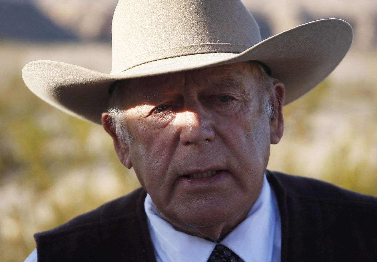 File - In this Jan. 27, 2016 file photo, rancher Cliven Bundy speaks to media while standing along the road near his ranch, in Bunkerville, Nev. Bundy, the renegade rancher at the center of a states versus federal rights fight, has made his first appearance in custody before a U.S. judge in Las Vegas. (AP Photo/John Locher, File)